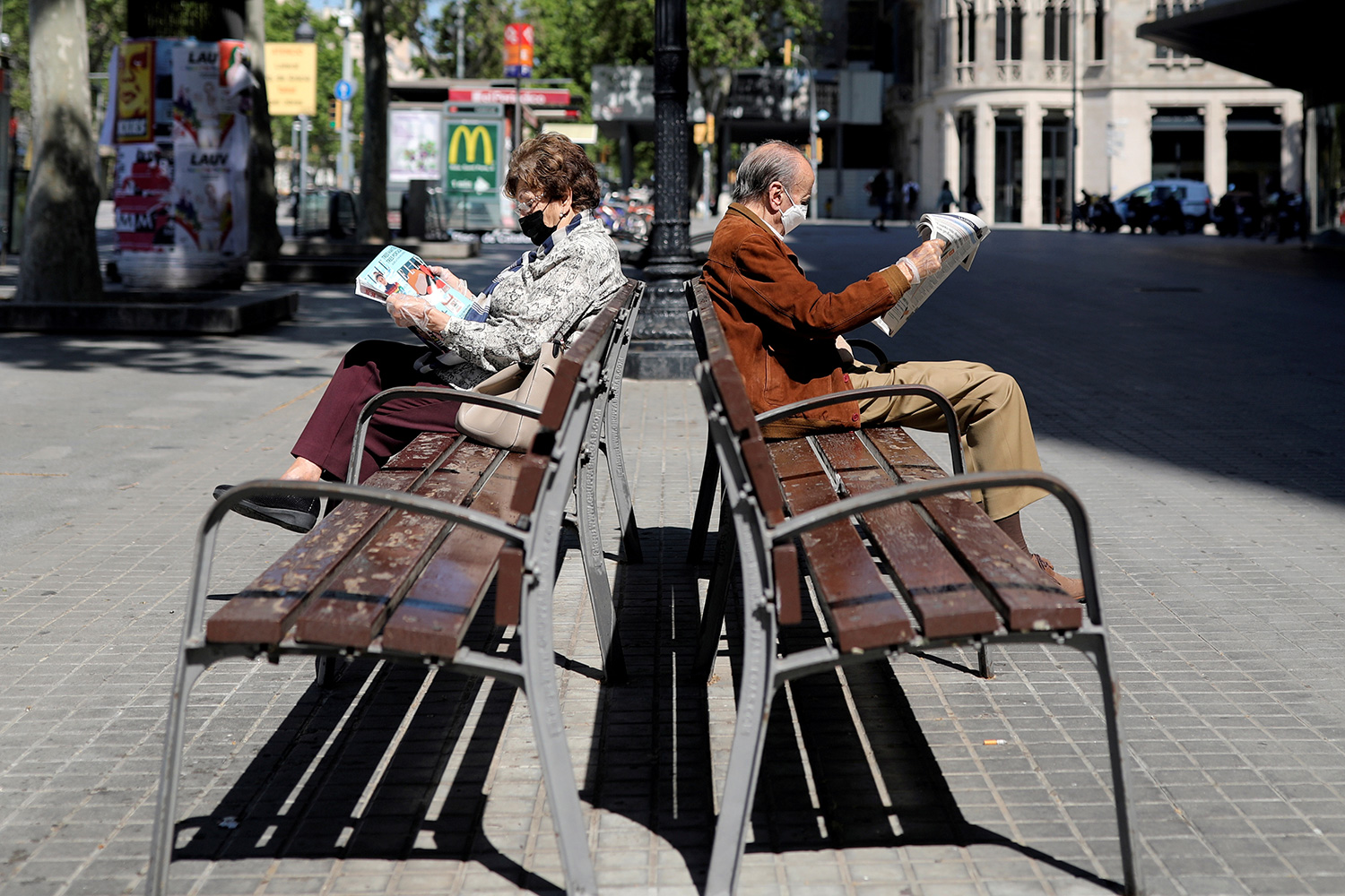 The picture shows two people on benches facing in opposite directions.