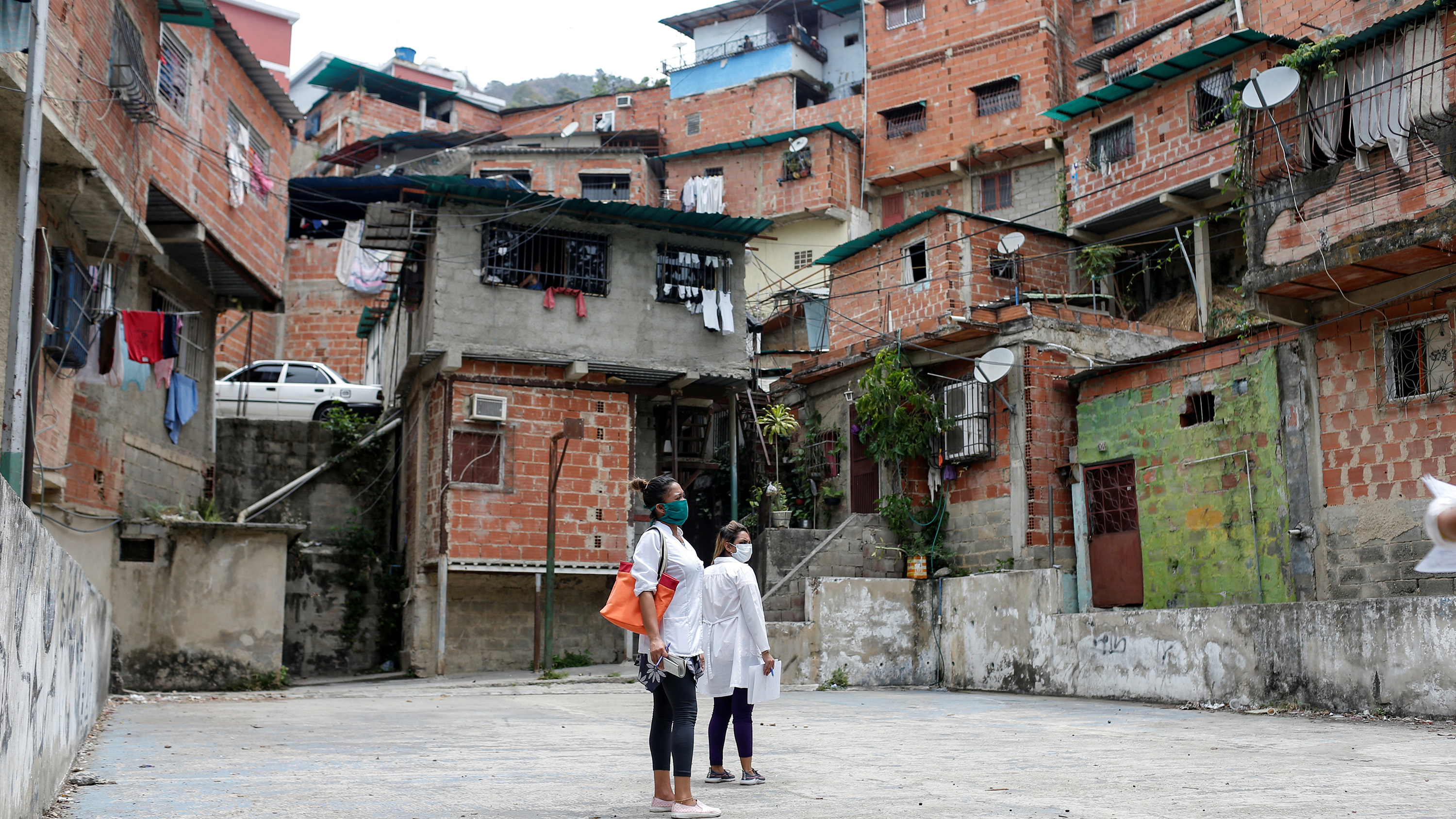 Picture shows two people standing before a huge neighborhood of towering ramshackle structures.