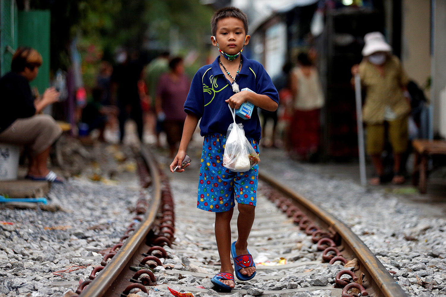 The picture shows a young boy holding a bag of food standing on railroad tracks.