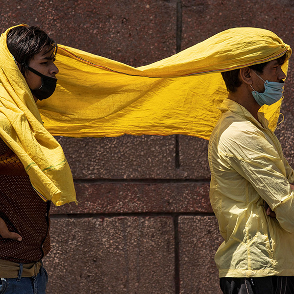 Migrant workers protect themselves from heat as they wait to board a train to their home state of eastern Bihar, at the end of the coronavirus lockdown in New Delhi, India, on May 21, 2020. The image shows two men sharing a yellow scarf. REUTERS/Danish Siddiqui