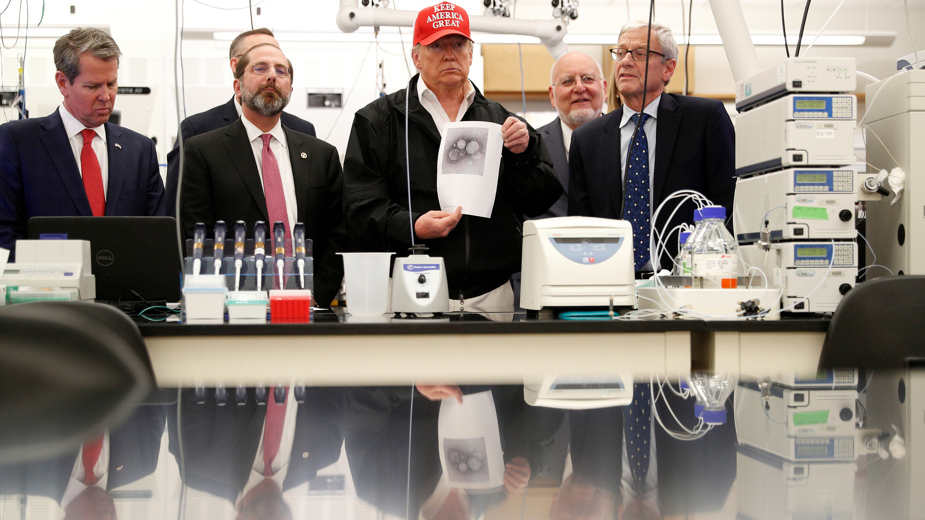 "The photo shows President Trump and several others in a laboratory setting. The president is wearing a red ""Make America Great Again"" hat."