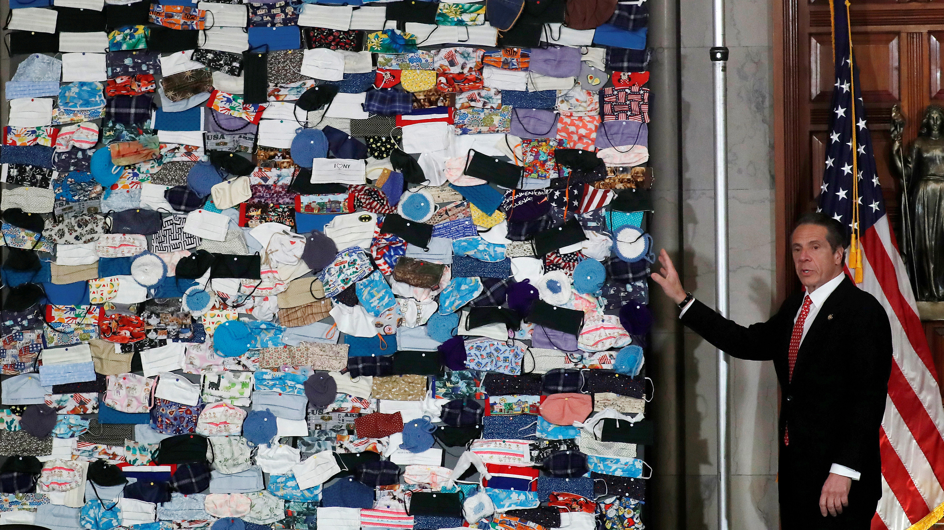 The photo shows the governor in front of a large quilted patchwork of masks.