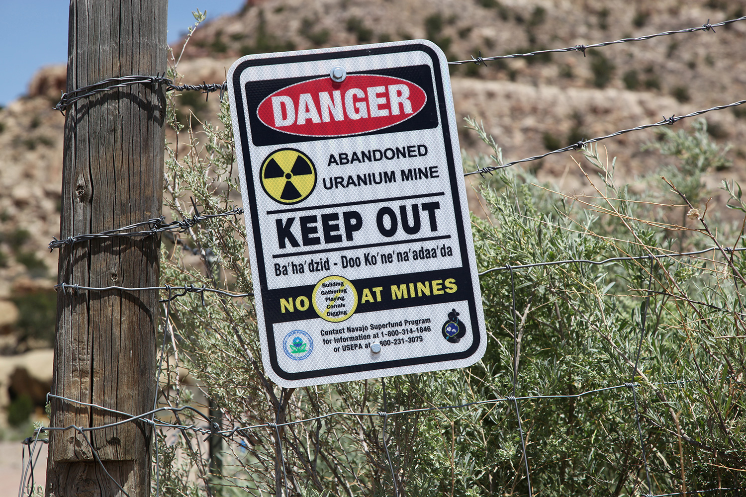 "Picture shows a sign on a fence in a remote-looking desert area warning people to ""KEEP OUT"" because of the dangers."