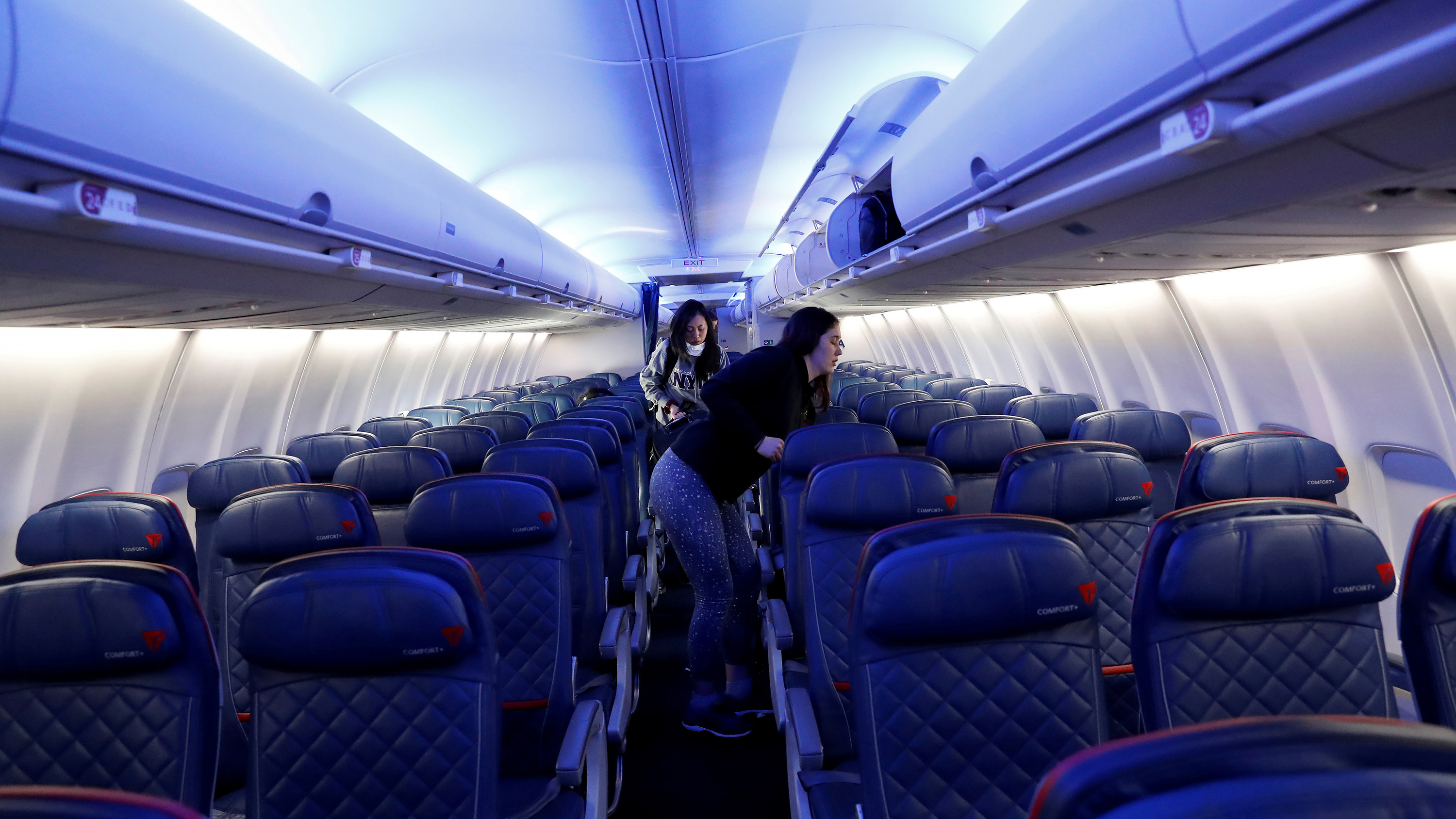 The photo shows a large jet passenger plane nearly empty of people.