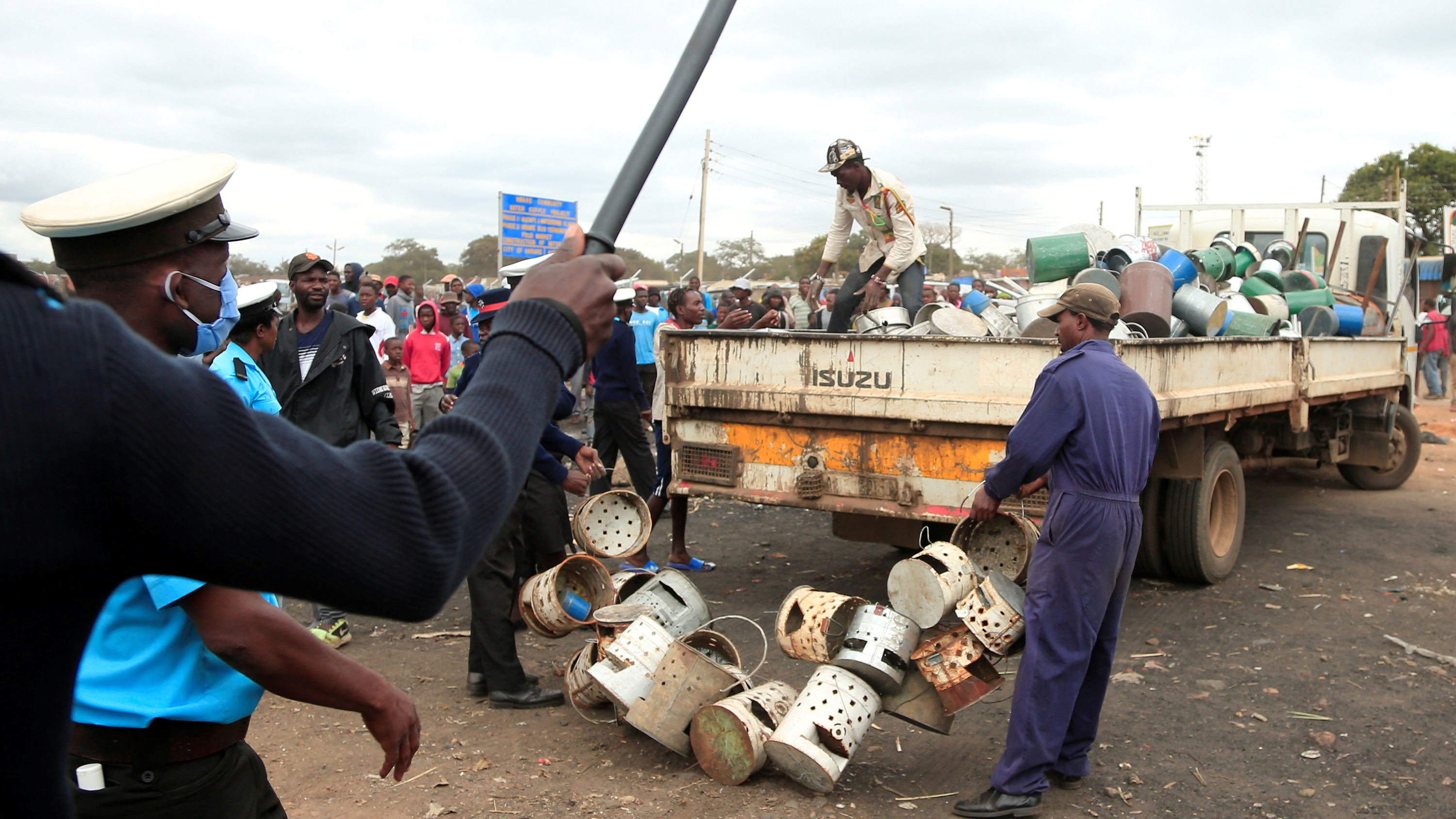 The photo shows a chaotic scene with a police officer waving a baton and people dragging crates and barrels onto a truck.