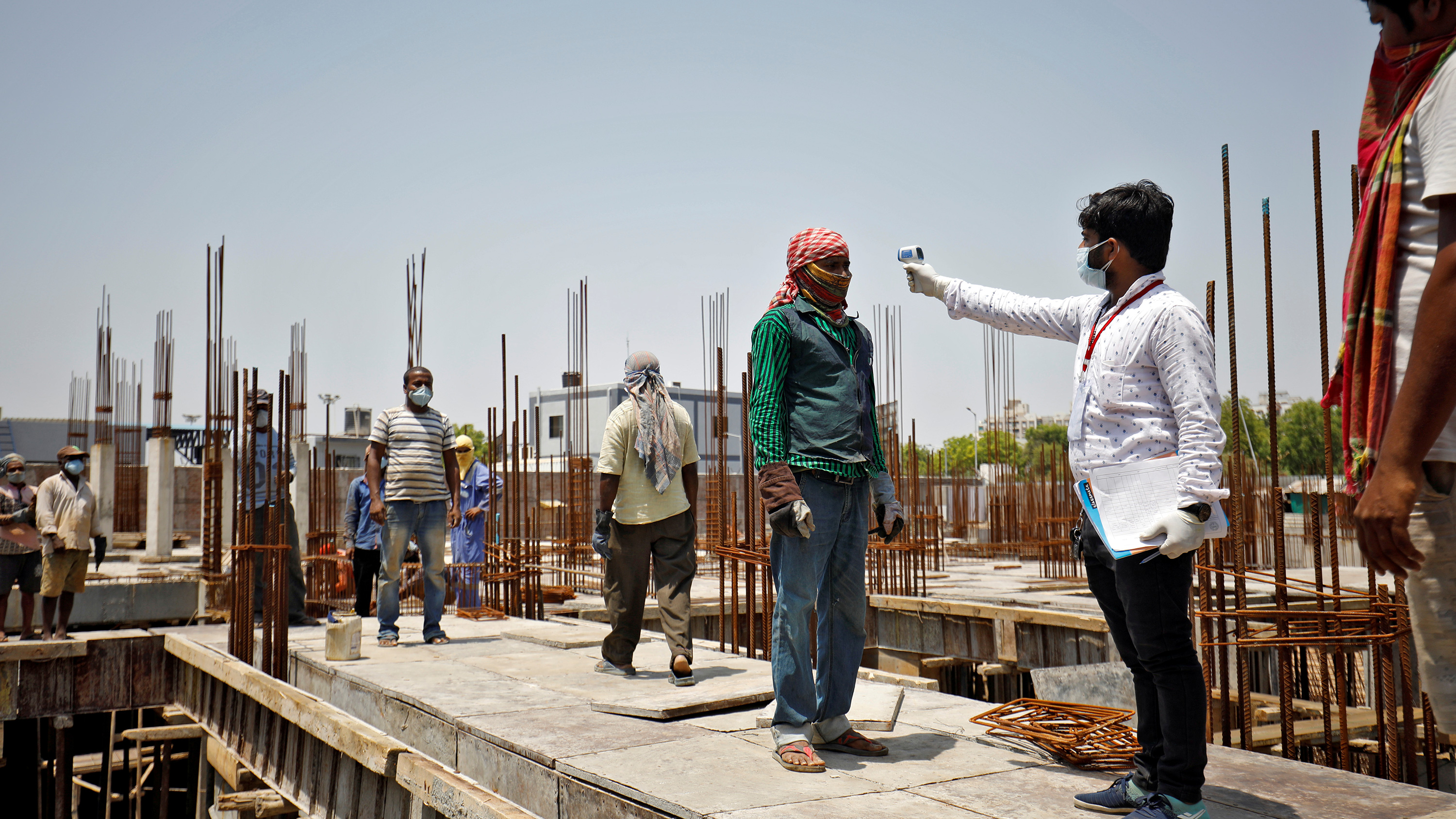 The photo shows the health worker aiming a temperature sensor at the forehead of a construction worker on site at a dig.