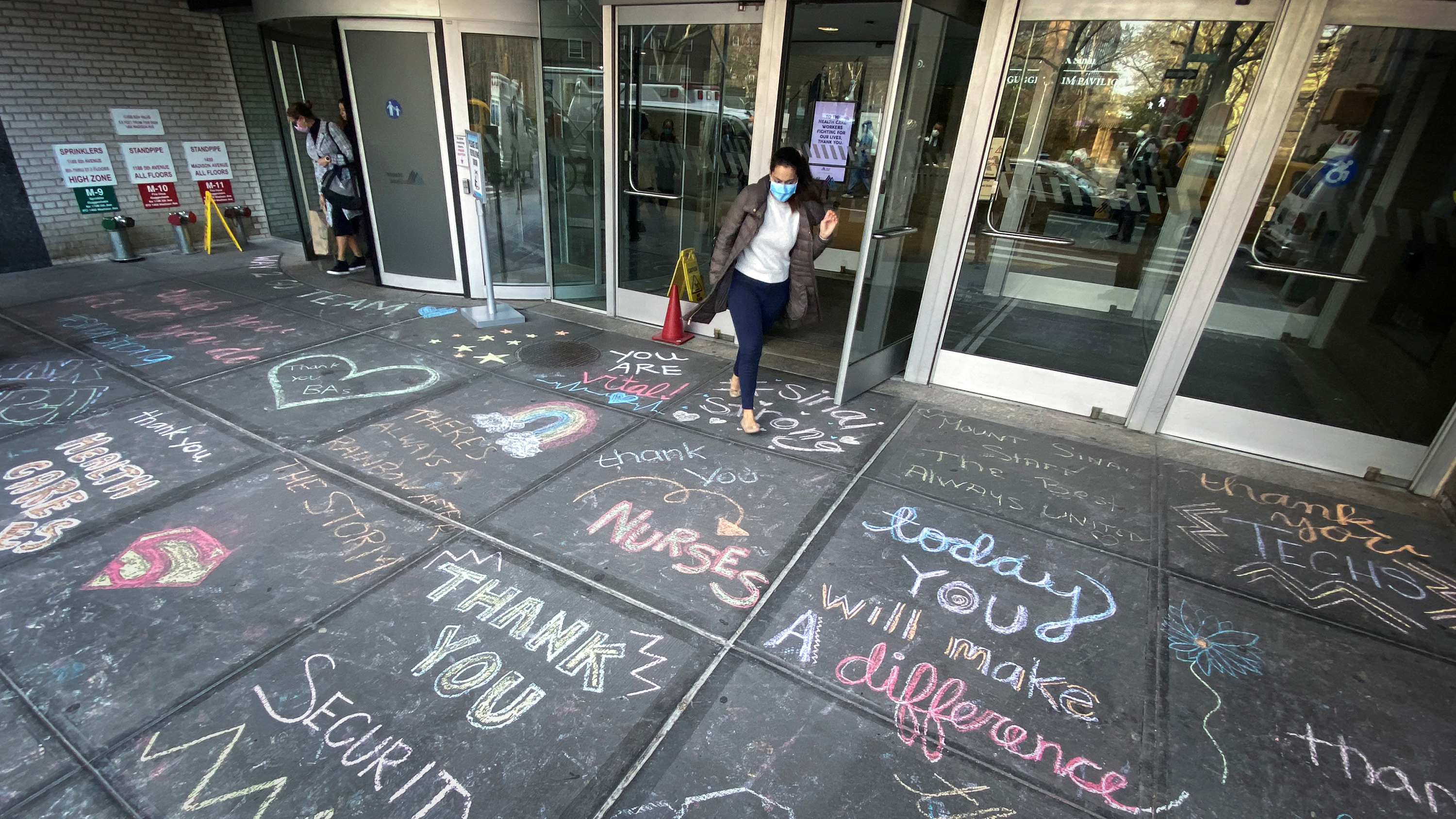 The photo shows an entrance to the hospital with a large number of colorful messages of thanks written in chalk on the sidewalk outside.