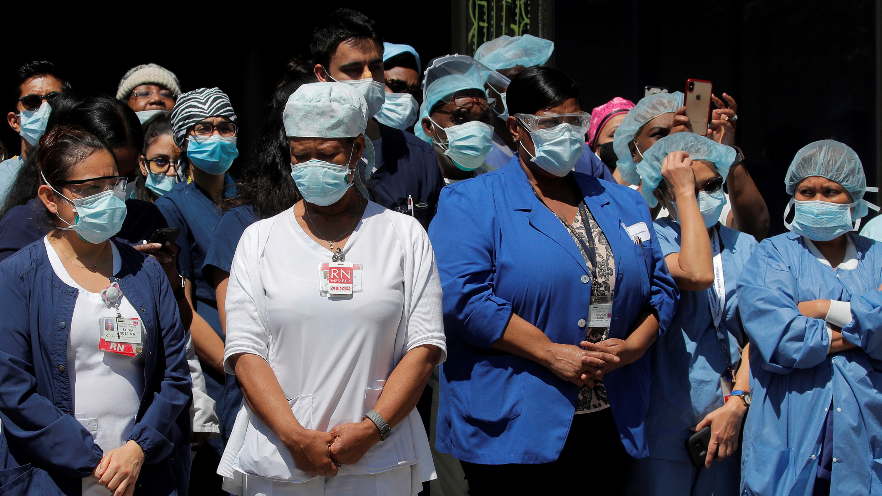 The photo shows a huge number of health workers standing quietly waiting.