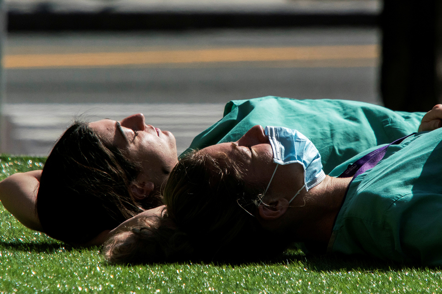 The photo shows two health workers laying on the grass in the warm spring sun.