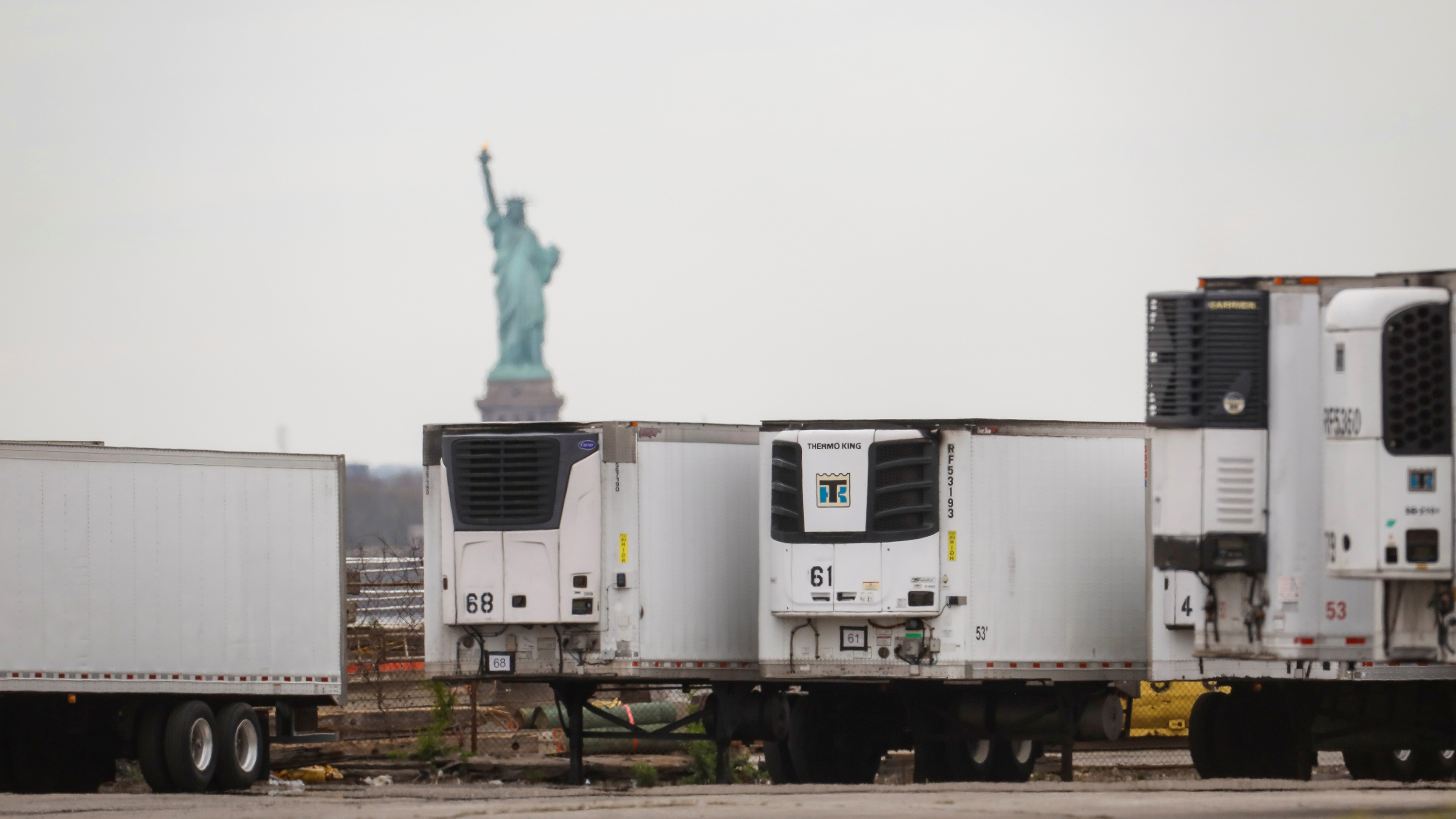 The photo shows several large 18-wheeler trucks parked with the Statue of Liberty in the background.