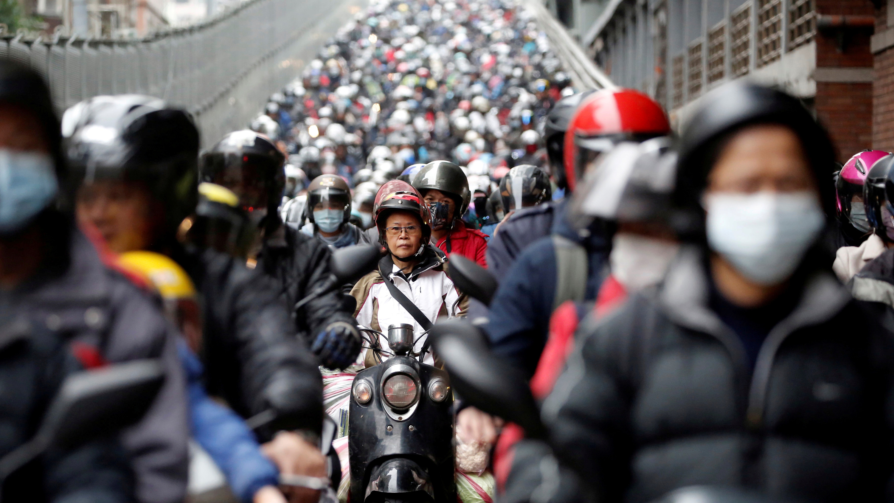 The photo shows a wide avenue filled with motorcycles heading toward the camera lens.