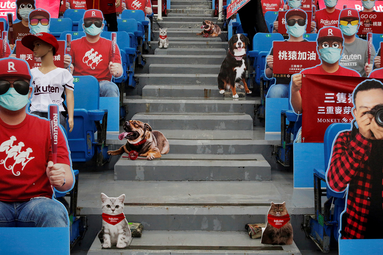 This is a very strange photo showing a section of seats at a sports venue filled with mannequins, cardboard cutouts and all manner of fake people.