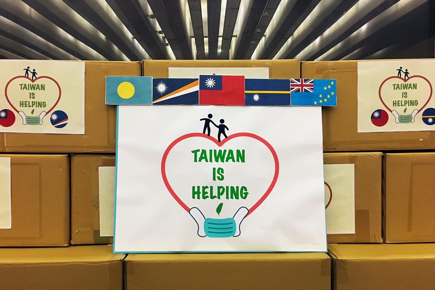 "The photo shows boxes stacked and decorated with country flags and a large sign that reads, ""Taiwan Is Helping."""