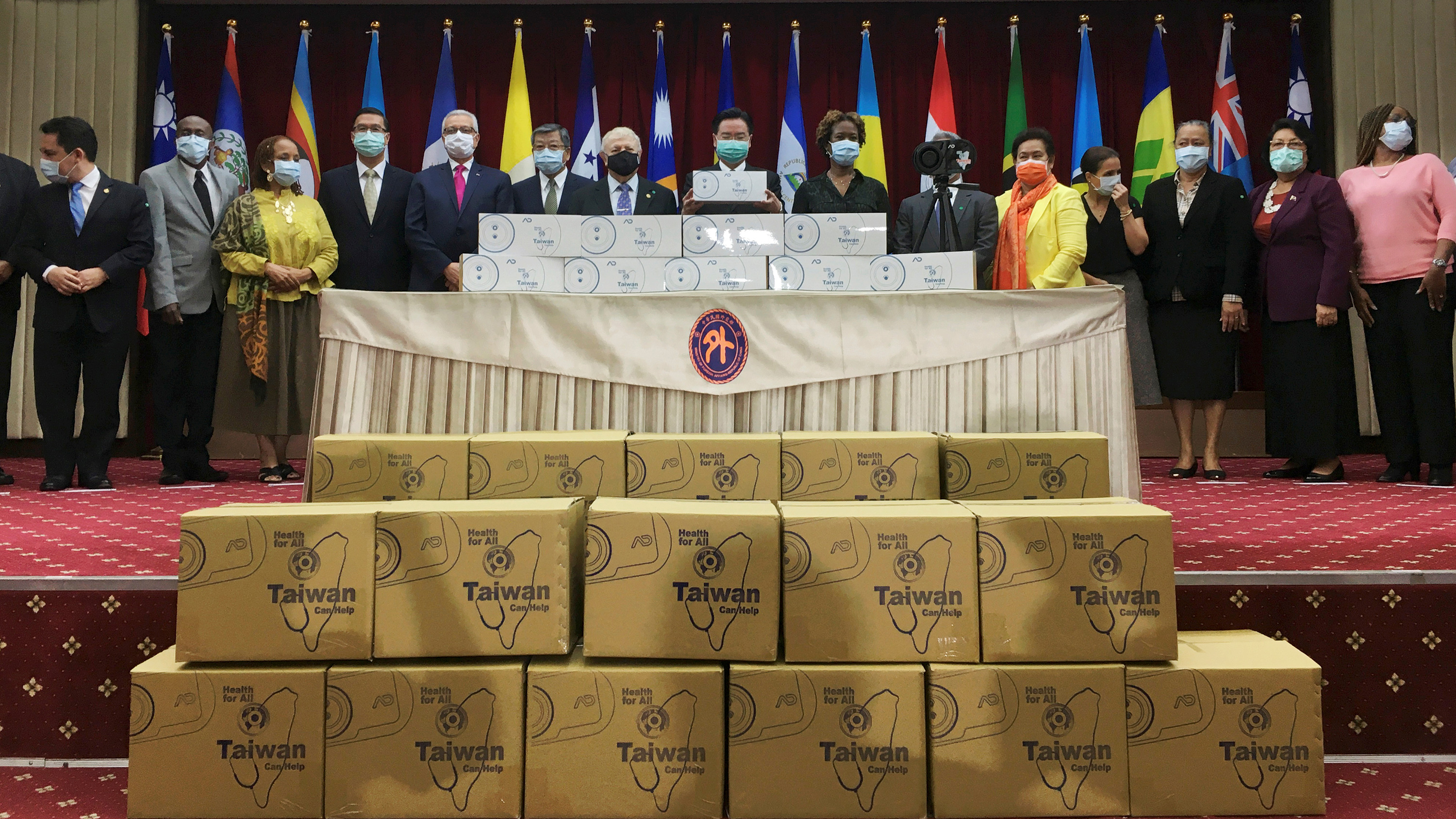 The photo shows a group of dignitaries amidst boxes of goods to be donated.