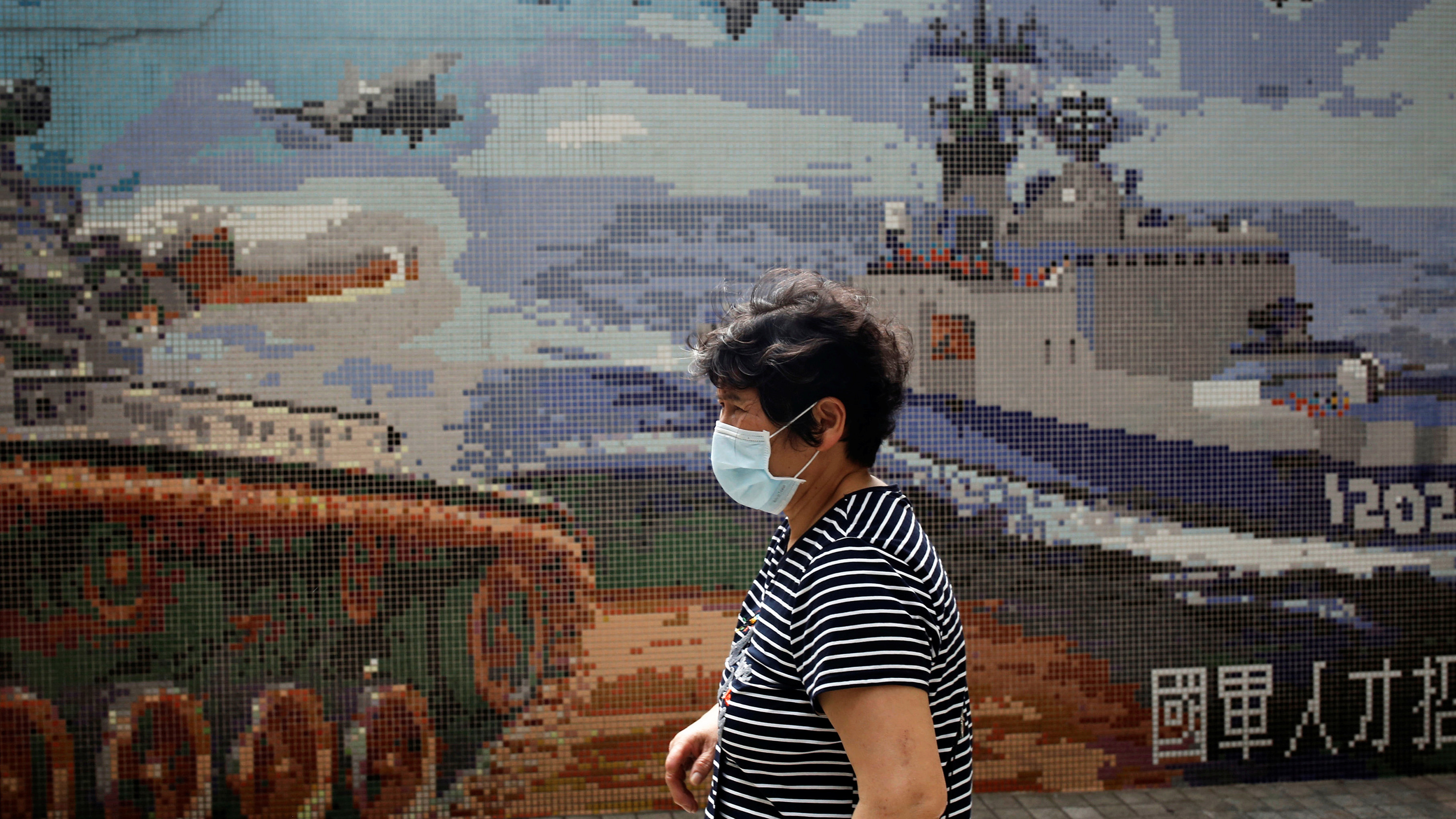 The photo shows a woman in a mask walking past a stylized poster showing war tanks, ships and planes.