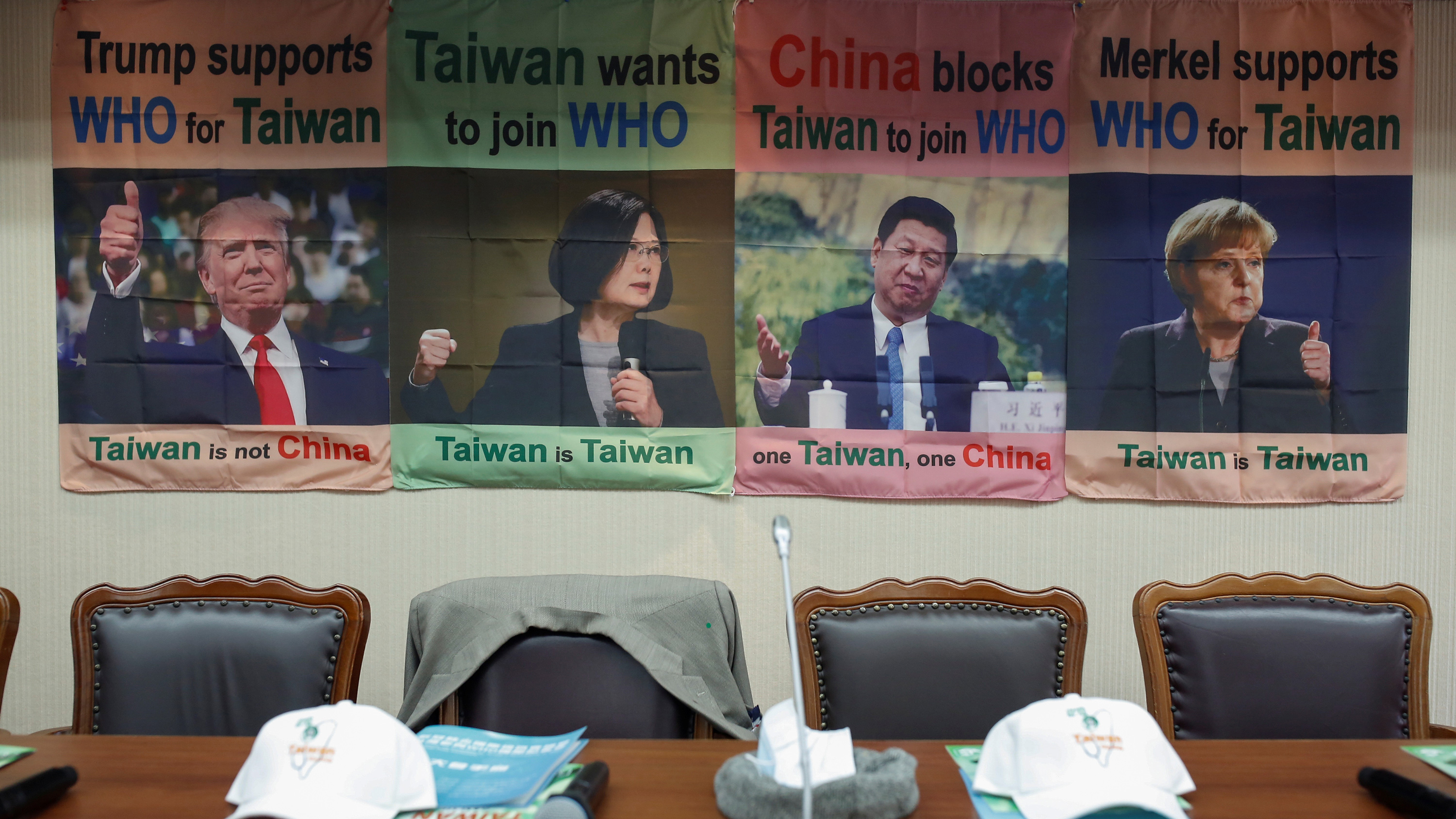 The photo shows empty seats, one with a jacket thrown over the back of it, with posters in the background showing testimonials by world leaders in support of Taiwan's WHO bid.