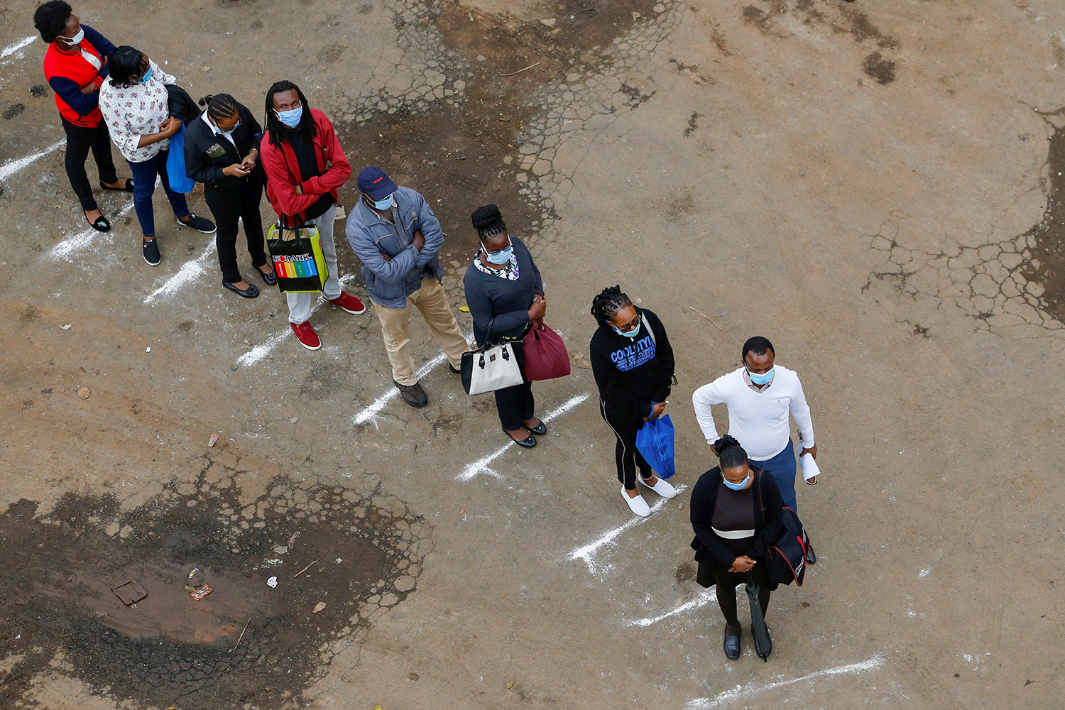 The photo shows several people standing in a line, separating themselves according to lines marked on the ground.