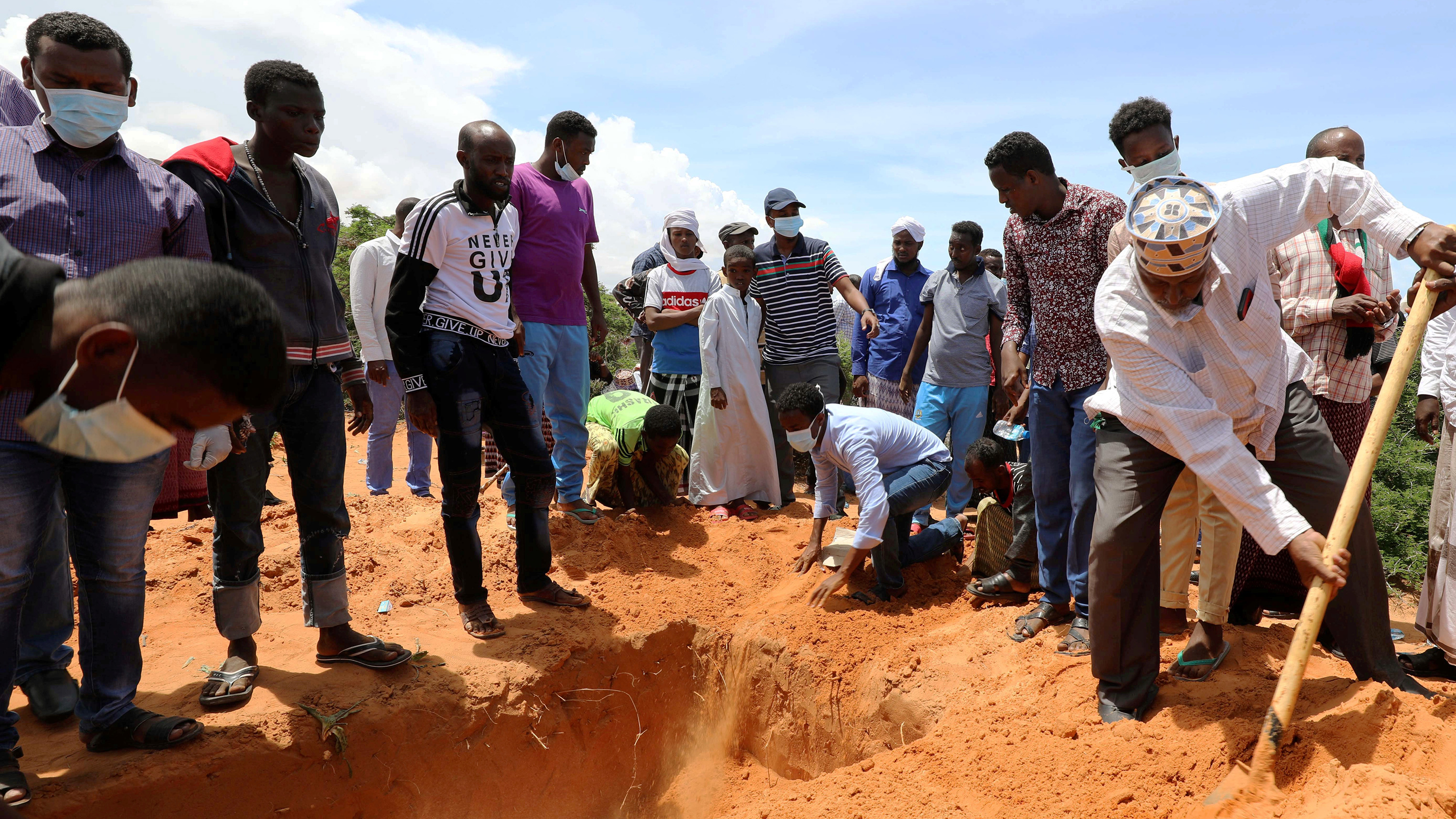 The photo shows a crowd gathered around a grave while one person shovels dirt in the hole.