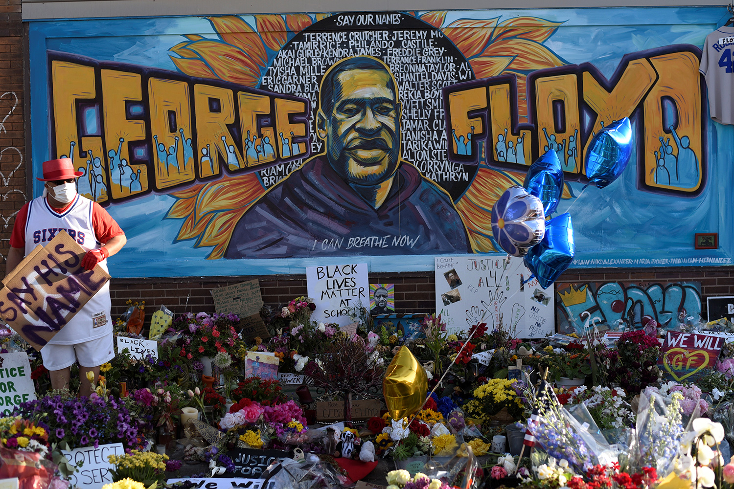 The photo shows a mural to Floyd with lots of flowers and signs laid out in front.