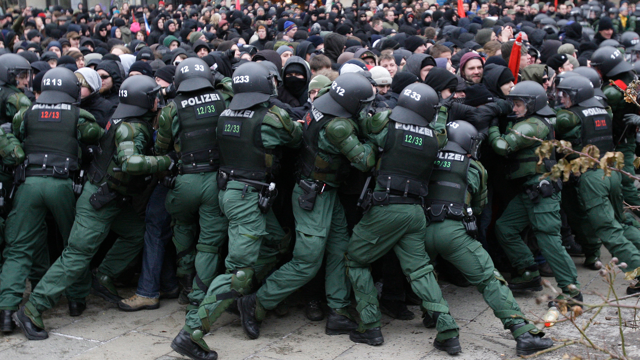 The photo shows a line of uniformed riot gear officers pushing hard against a scrum of protesters.