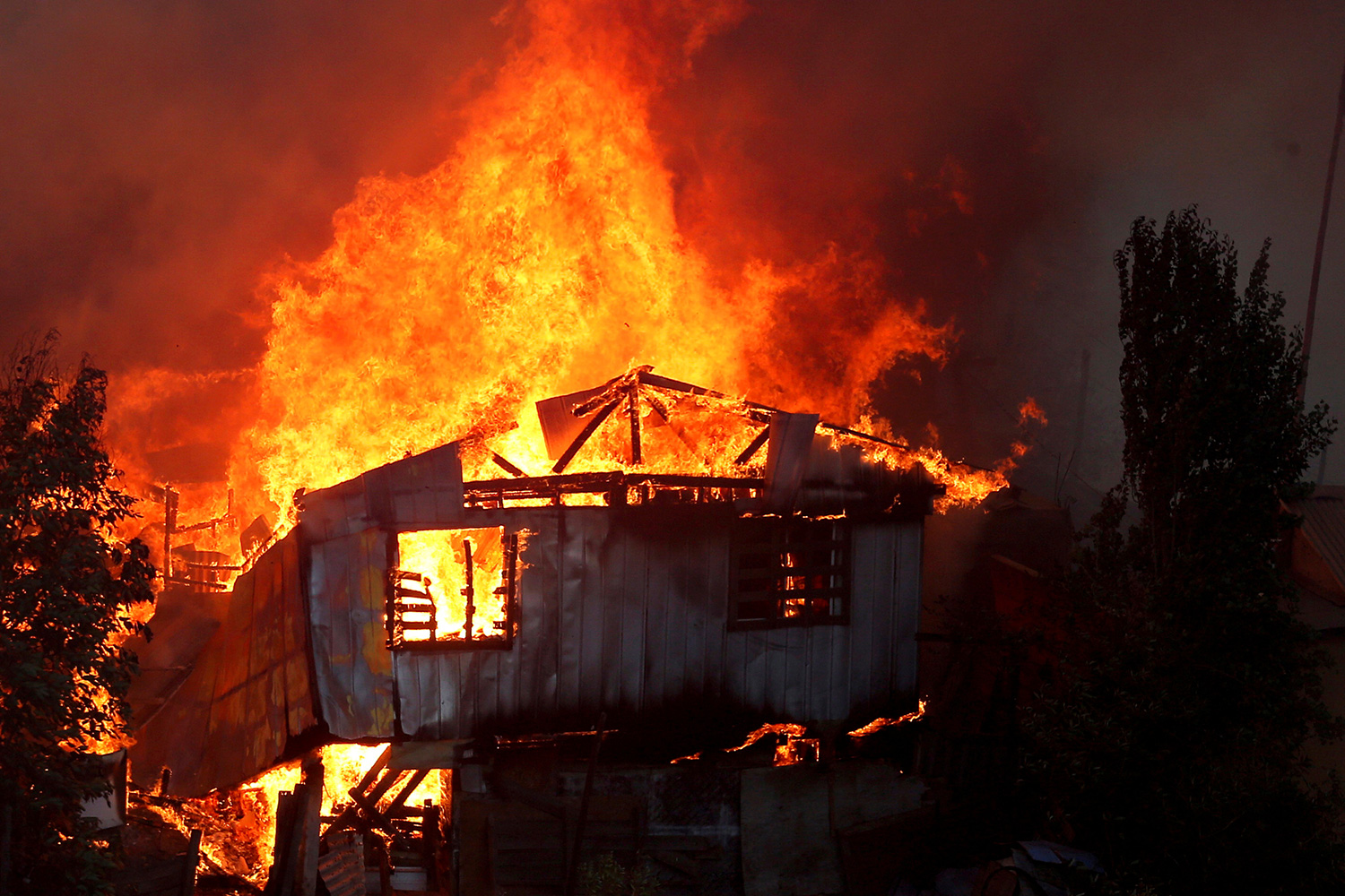 The photo shows a house engulfed in flames.