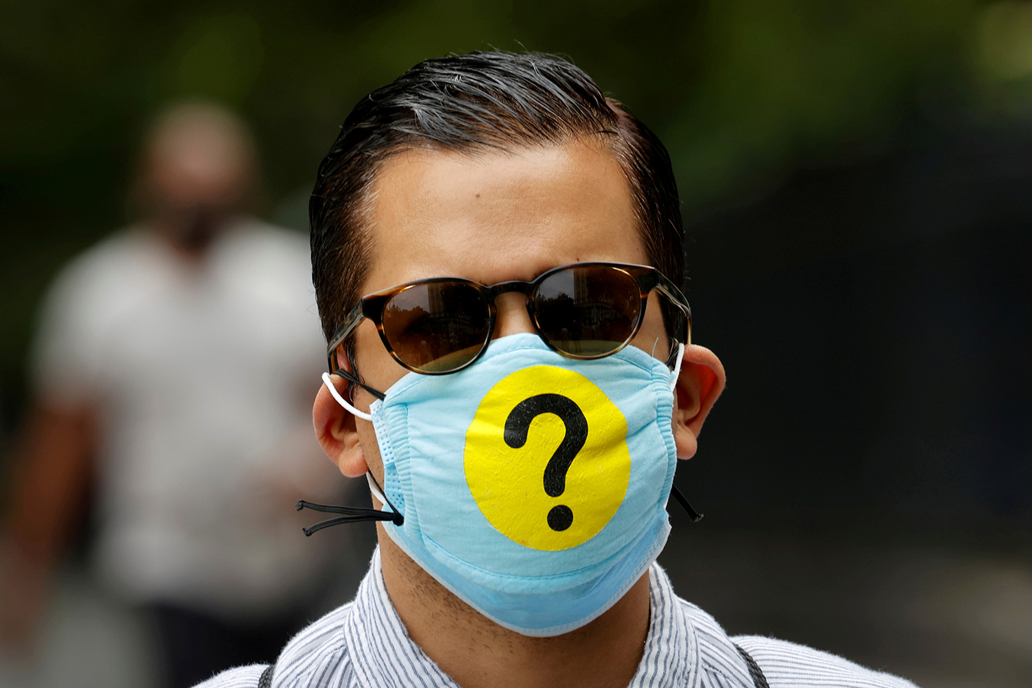 A man wears a protective facemask decorated with a question mark in lower Manhattan during the outbreak of the coronavirus disease (COVID-19) in New York, U.S., May 22, 2020. Picture shows a well groomed man who appears to be in his 30s wearing a mask adorned with a huge question mark. REUTERS/Mike Segar