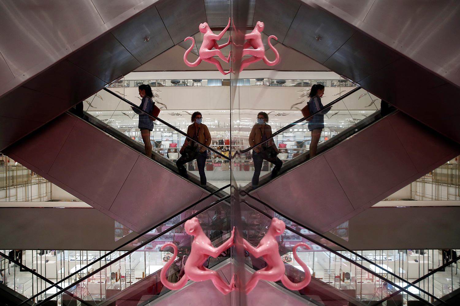 Customers wearing facemasks are reflected in a mirror as they stand on an escalator inside the department store Le Printemps Haussmann in Paris, France, amid the coronavirus pandemic on May 28, 2020. The photo shows people on an escalator with the photo showing mirror images on the left and right of the frame. REUTERS/Gonzalo Fuentes