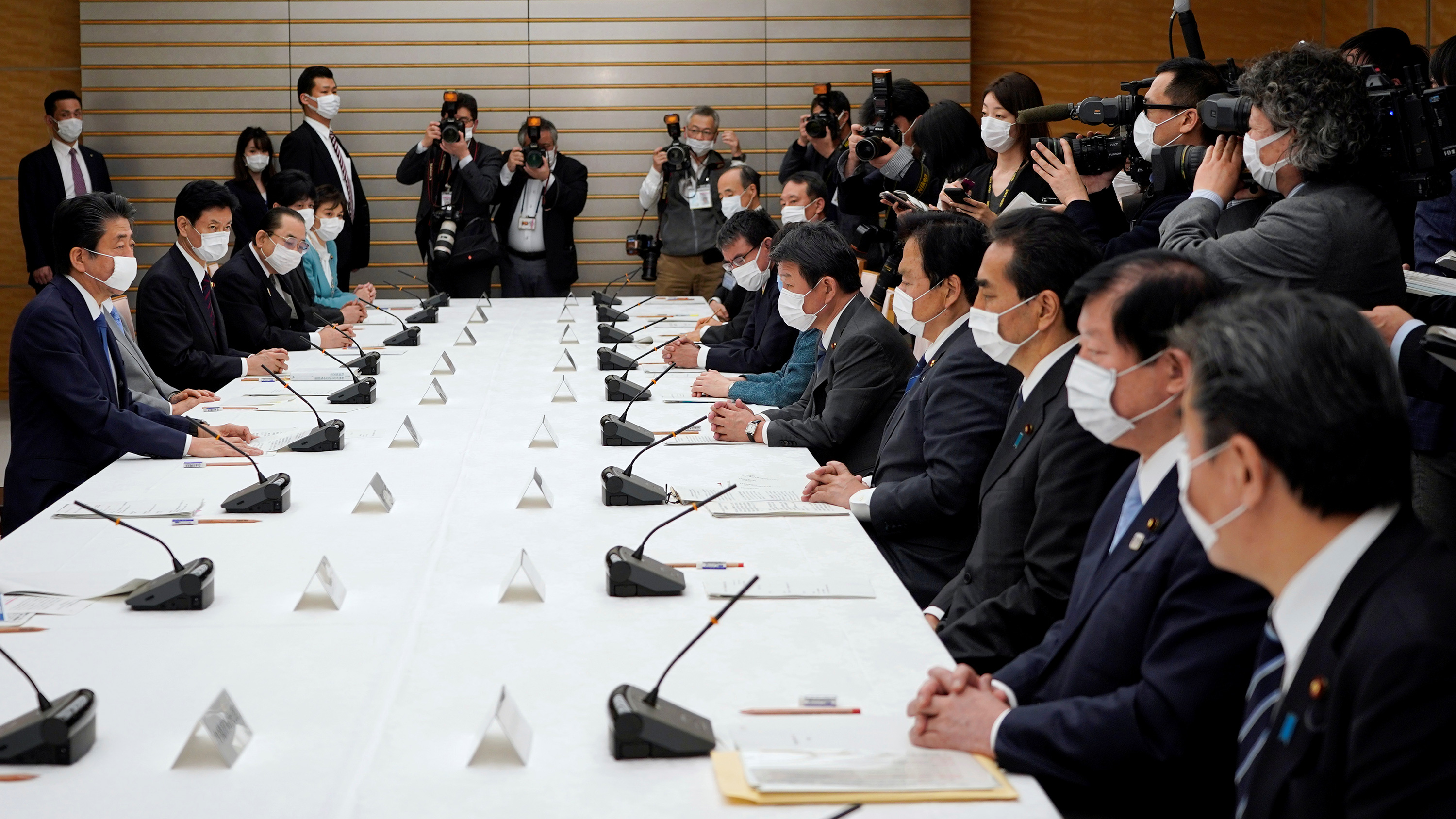 The photo shows the PM and a number of government ministers sitting around a large table. Reporters are seen at the edge of the frame snapping photos. Everyone in the picture is wearing a mask.