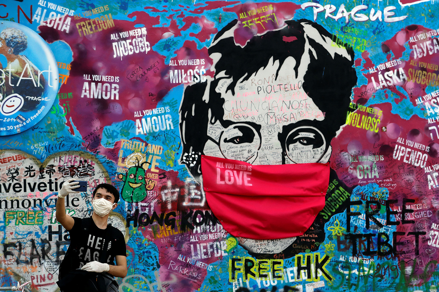 A man wearing a facemask takes a selfie in front of the legendary graffiti-covered John Lennon Wall as the coronavirus pandemic continues in Prague, Czech Republic, April 6, 2020. The photo shows a large graffiti mural of the legendary singer and peace activist with a mask draped over Lennon's face. A mane in the foreground holds his device at arm's length taking a selfie. REUTERS/David W Cerny