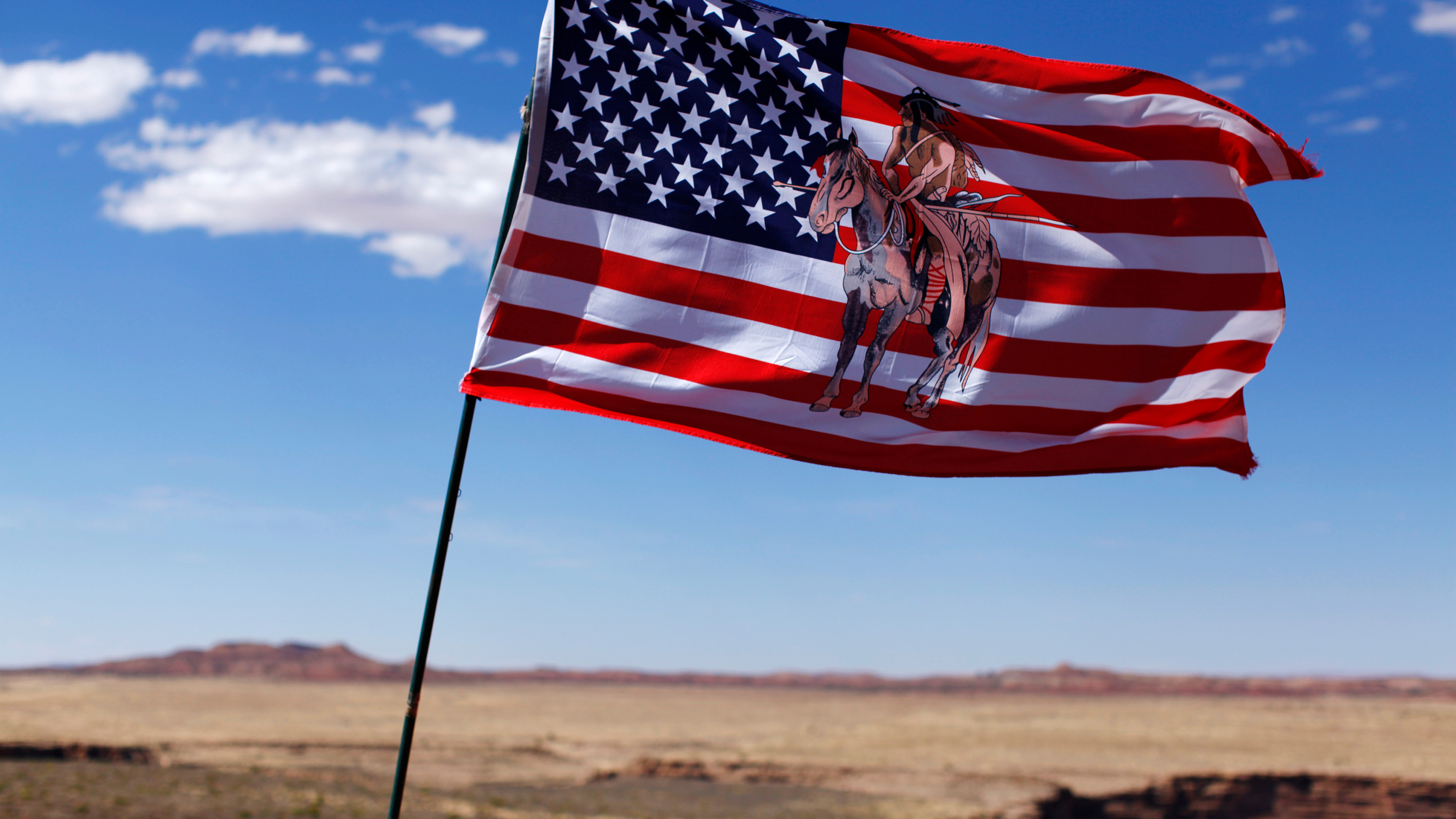 The photo shows a flag blowing in the wind with an Indian horse rider on the flag.