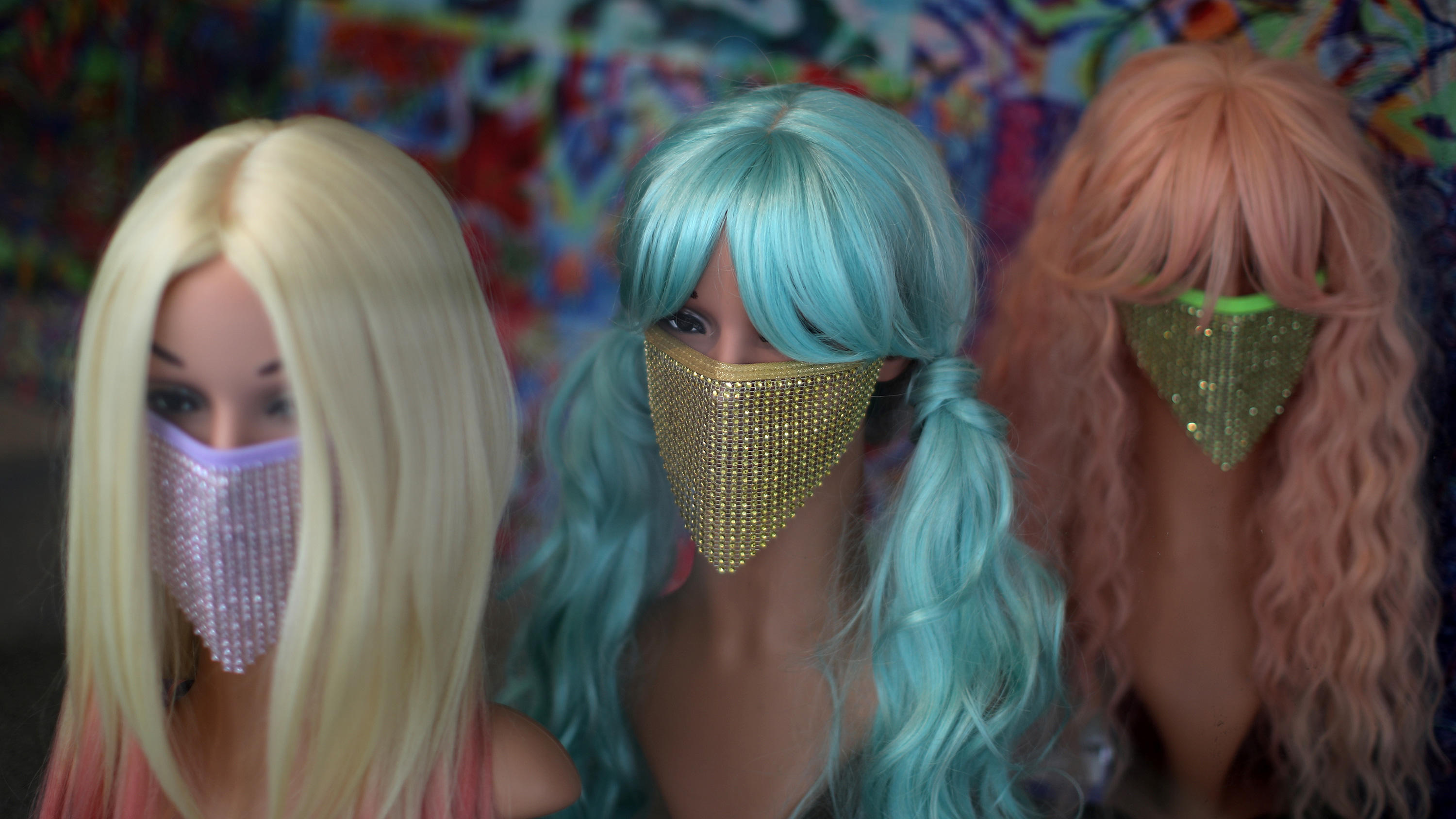 The photo shows three mannequin heads, each with a colorful wig as well as a colorful, sequined mask.