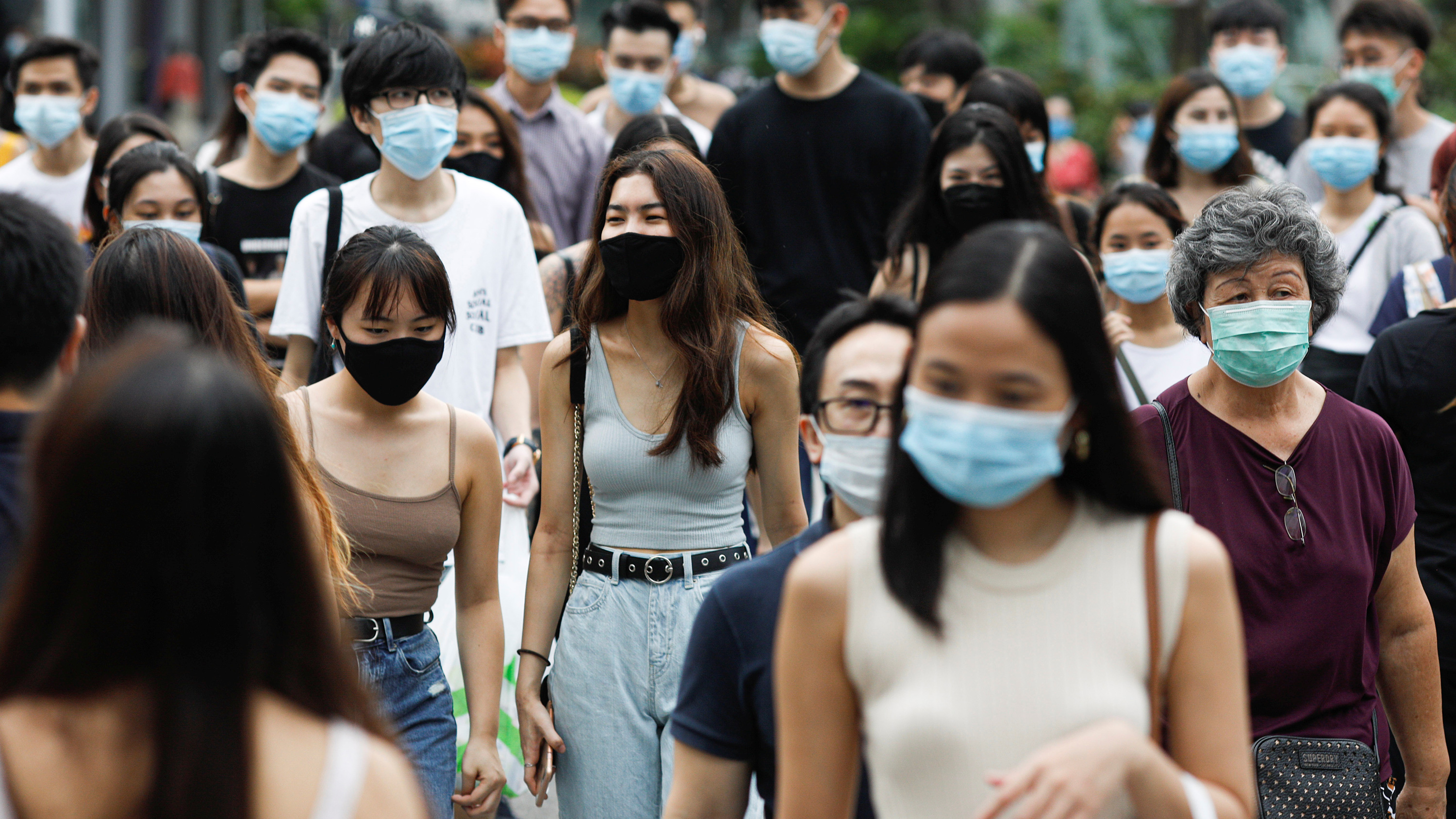 The photo shows a busy street bustling with foot traffic, and strikingly every single person appears to be wearing a mask. The photo shows