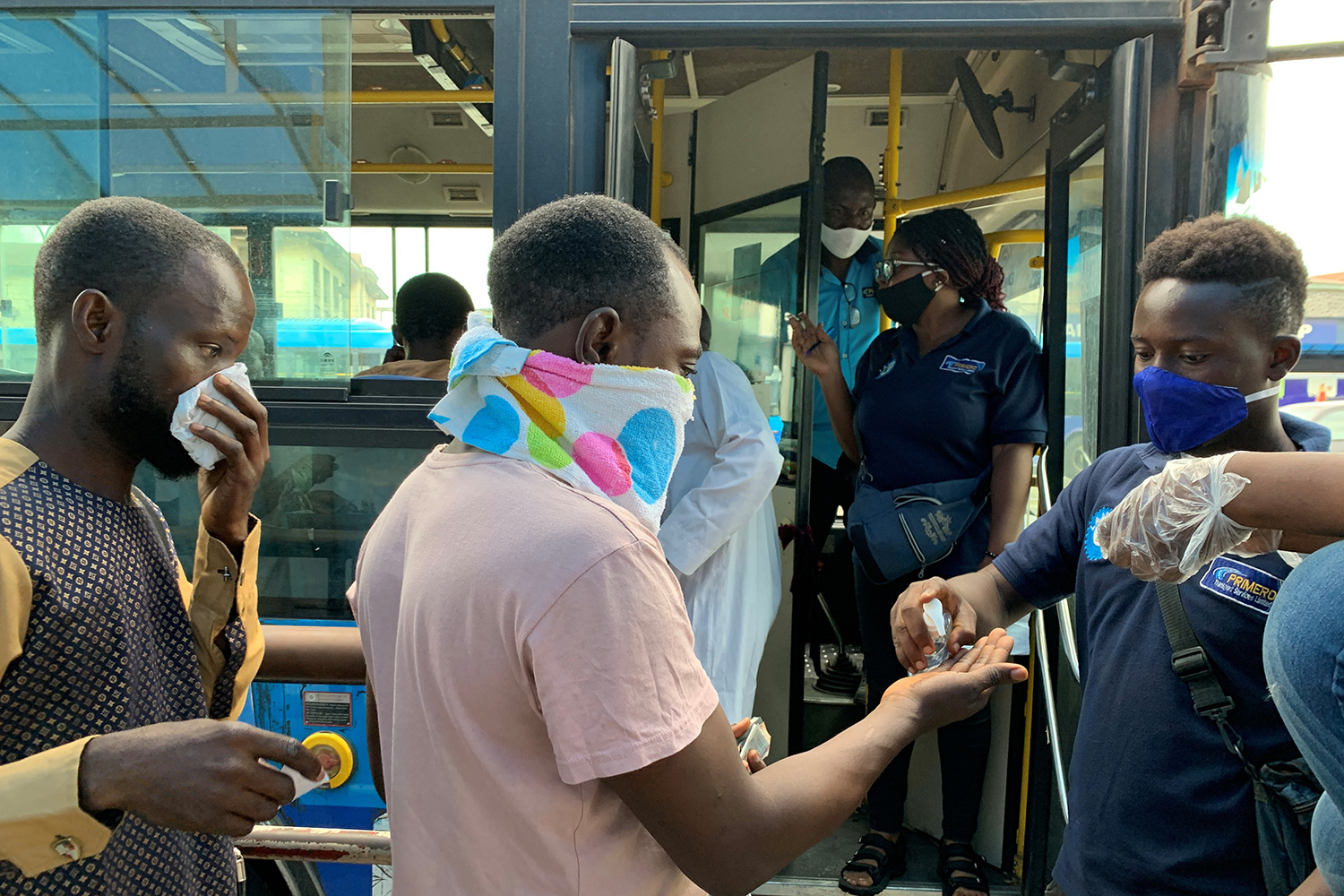 Public transport bus staff offers hand-sanitizer to a passenger who is about to board the bus on the first day of the easing of the lockdown measures during the outbreak of the coronavirus disease (COVID-19) in Lagos, Nigeria May 4, 2020. The photo shows a bus driver dispensing sanitizer to passengers as they board. REUTERS/Temilade Adelaja