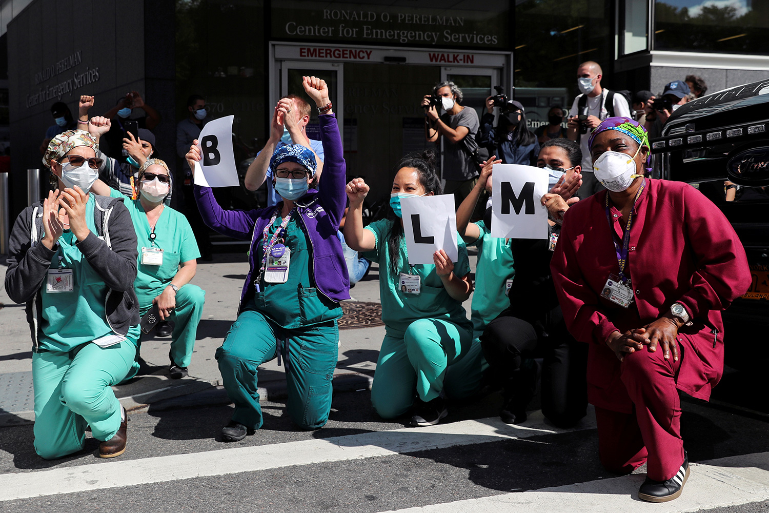 The photo shows a number of health workers taking a knee in protest.