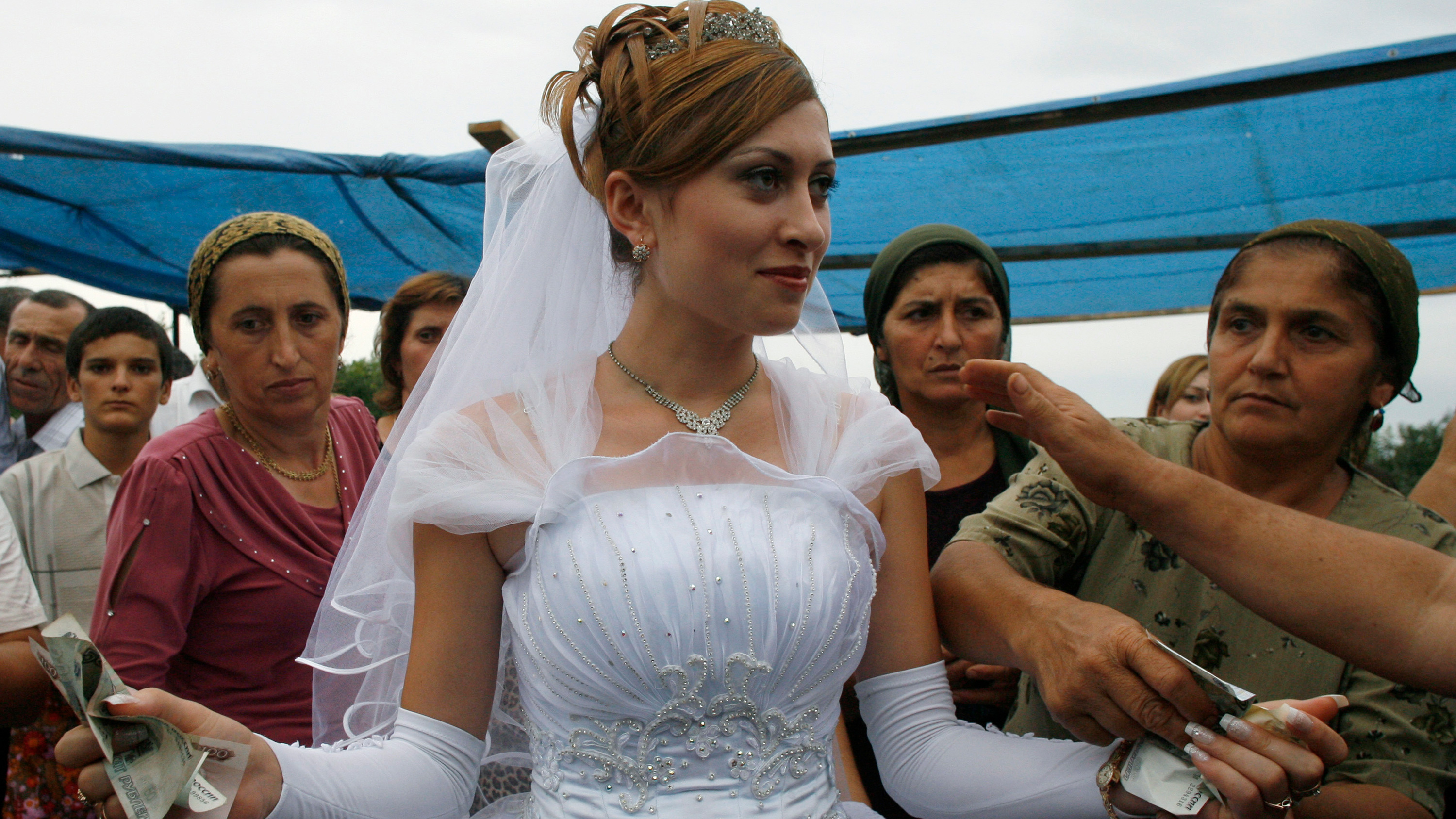 The photo shows a bride at the center of the frame surrounded by older women.