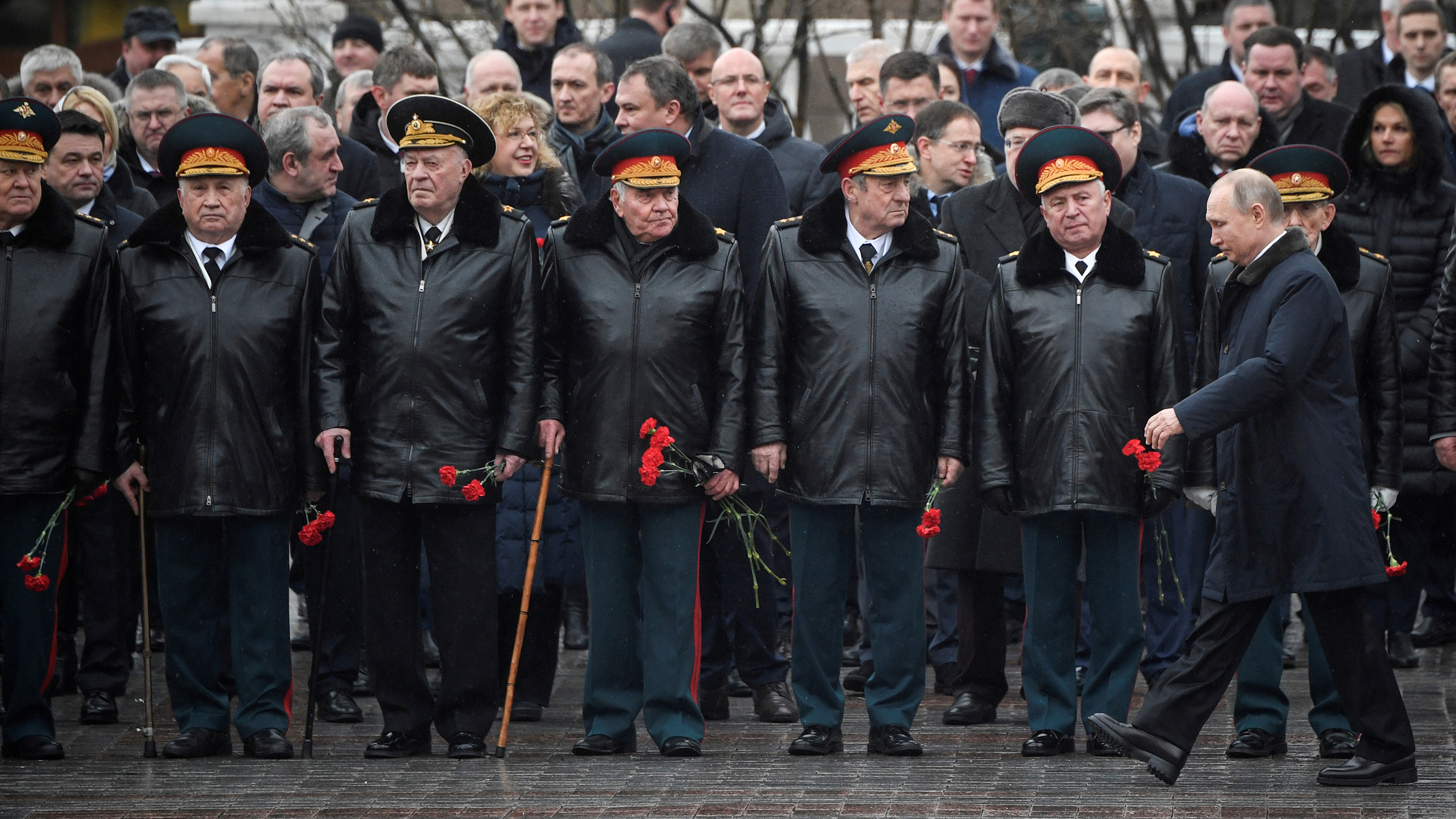 The photo shows Putin walking past a line of military top brass.