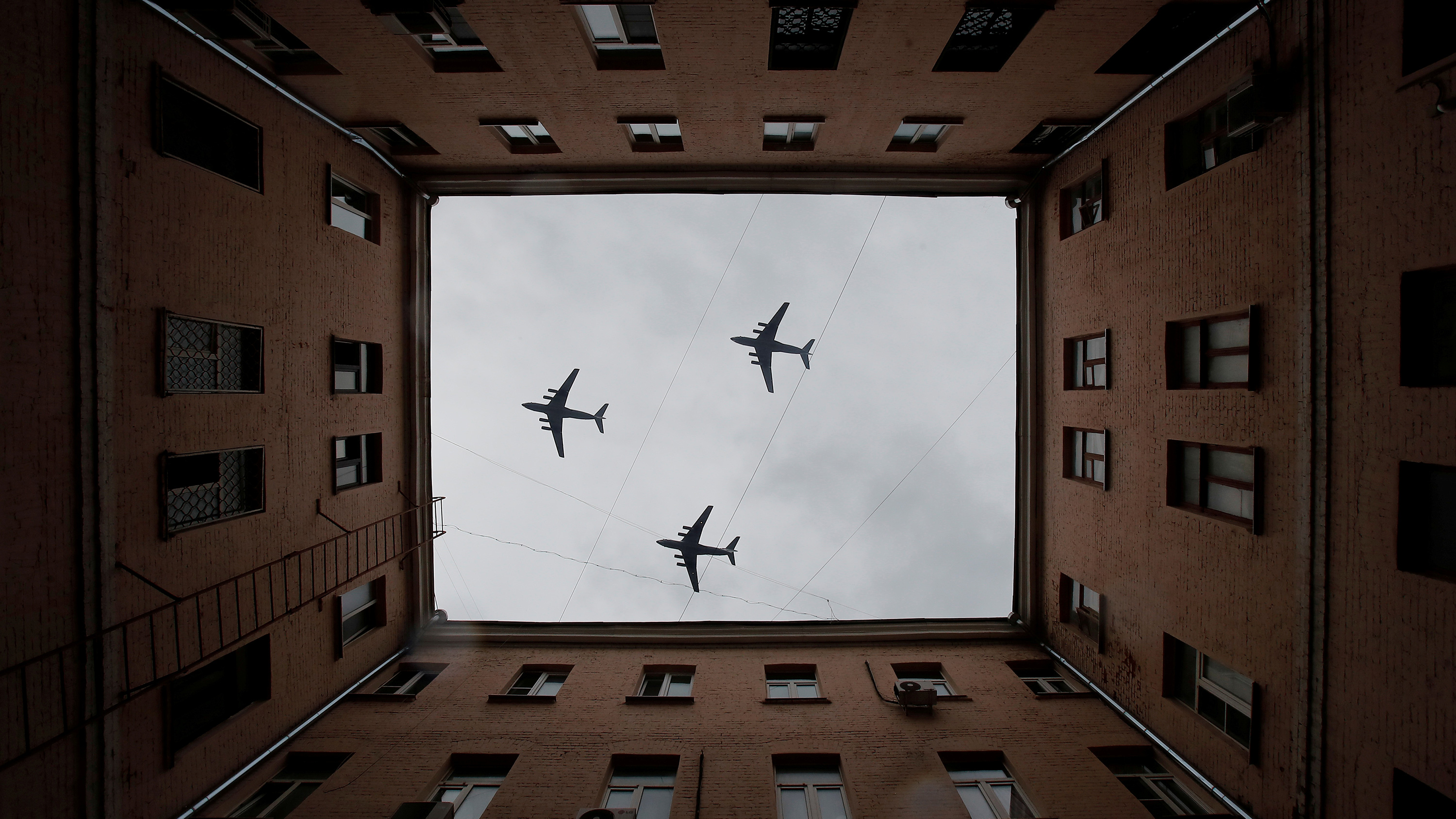 The striking image shows three planes photographed looking up througg the open courtyard of a large apartment-style building.