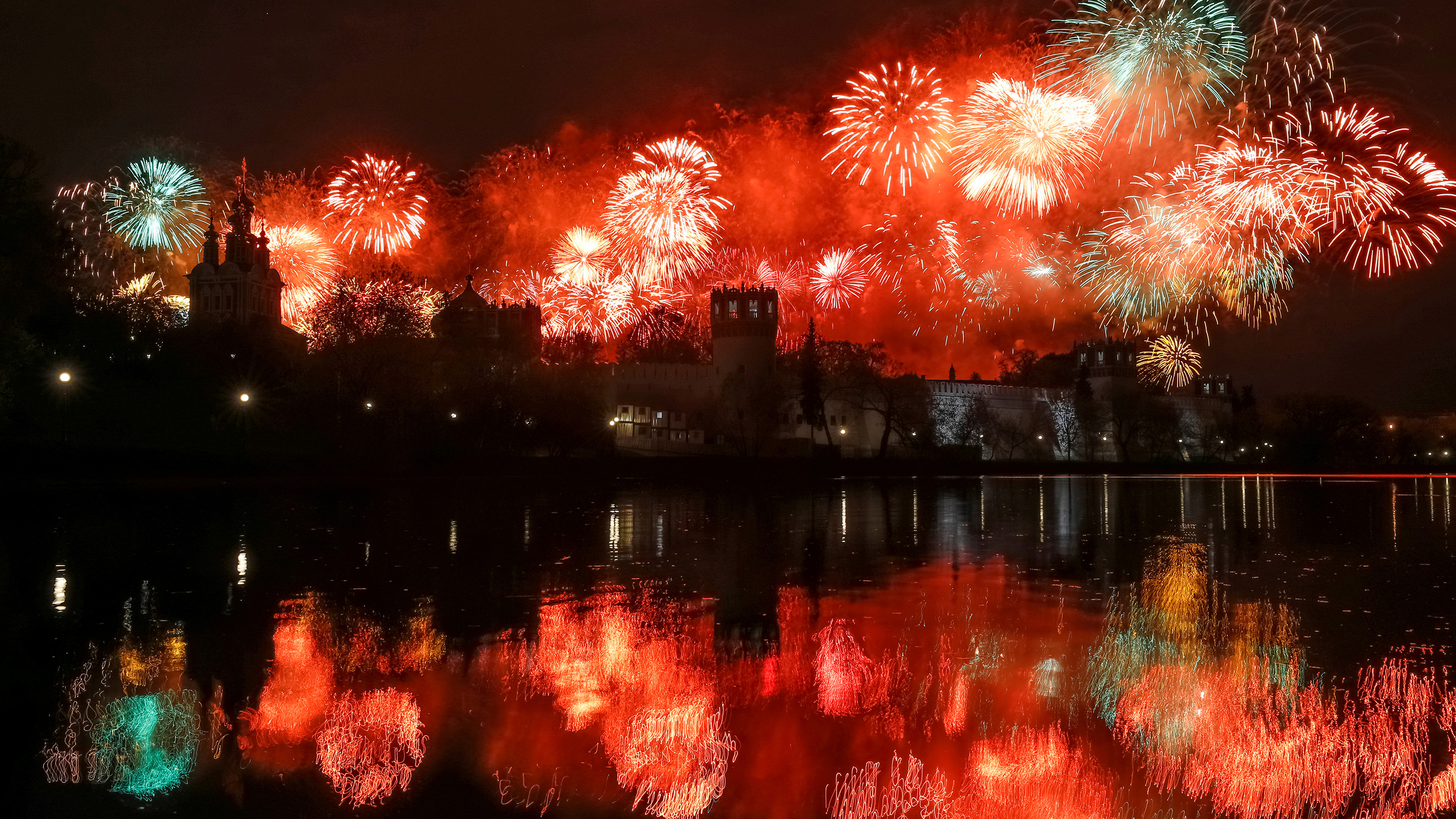 This is a striking photo showing a huge number of fireworks exploding behind a magnificent monastery and reflected on the river facing the camera.