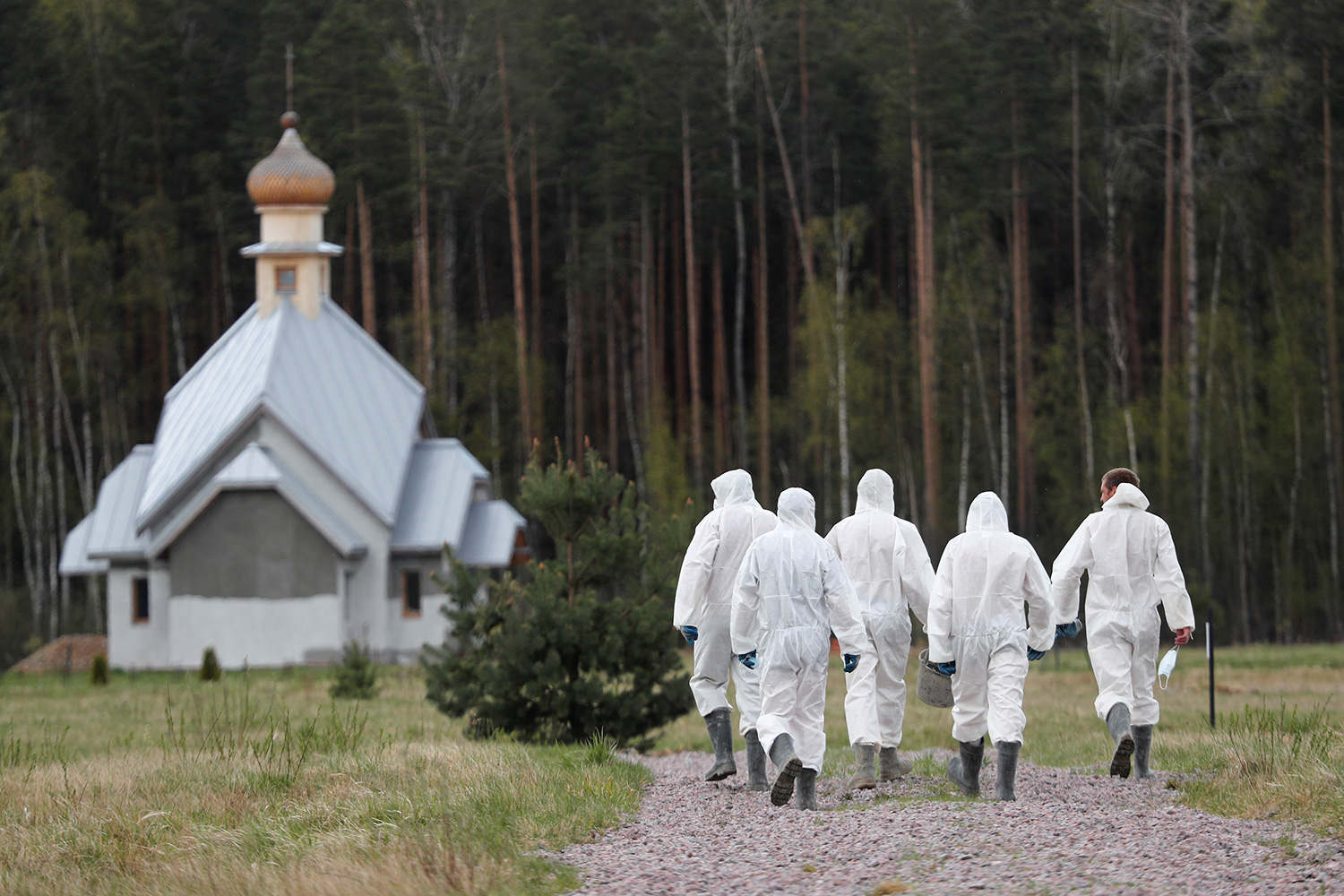 The photo shows a group of grave diggers wearing personal protective equipment walking weith their backs to the camera towards an old church.