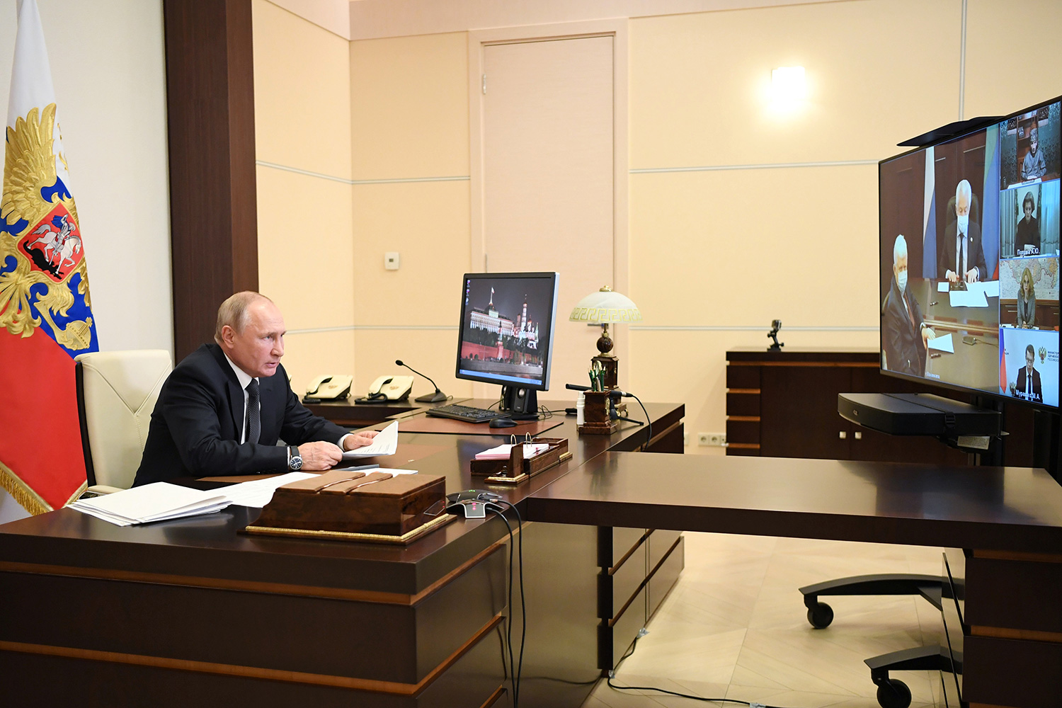 The image shows Putin at a desk across from a large screen on which others can be seen conferenced in.