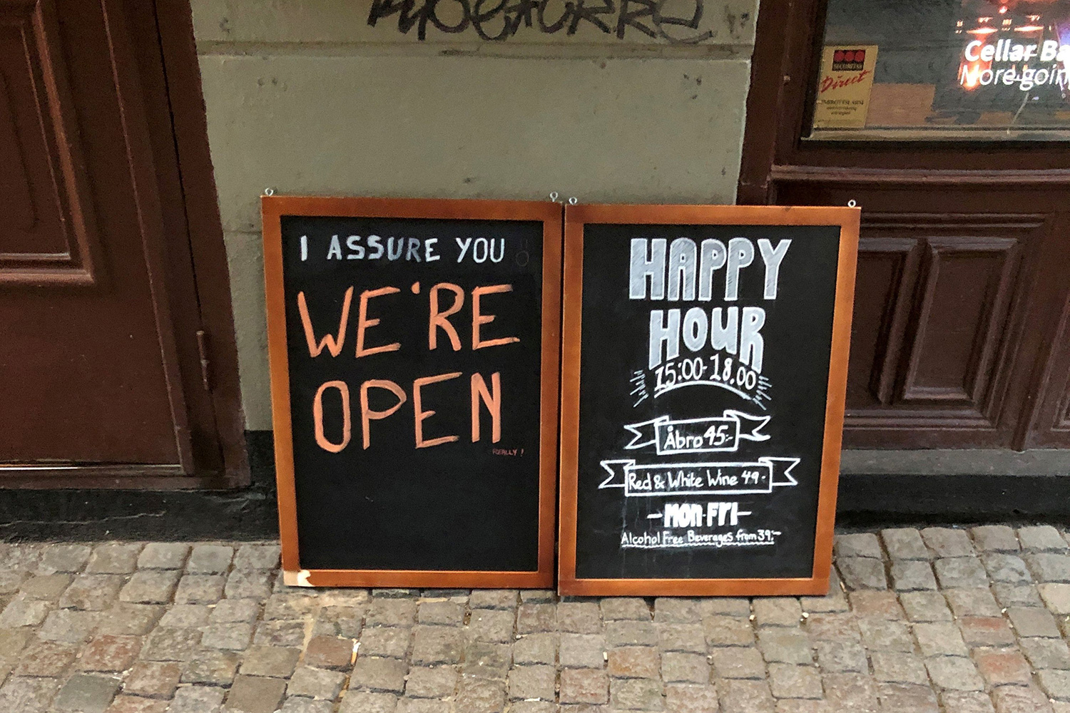 "The photo shows a chalk sign in front of a bar that reads, ""We're Open."""