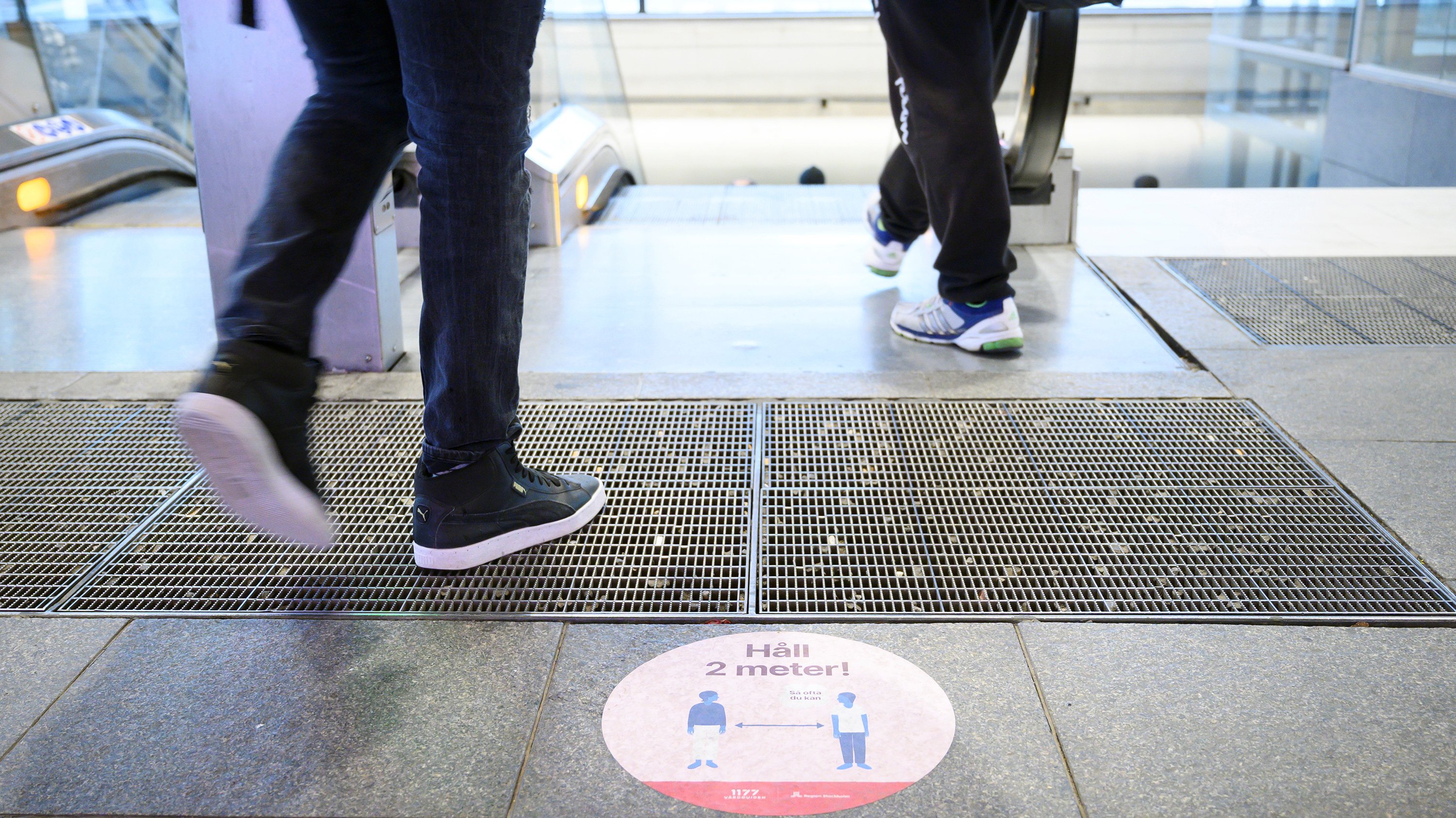 The photo shows feet walking onto an escalator above a sign warning of social distancing.