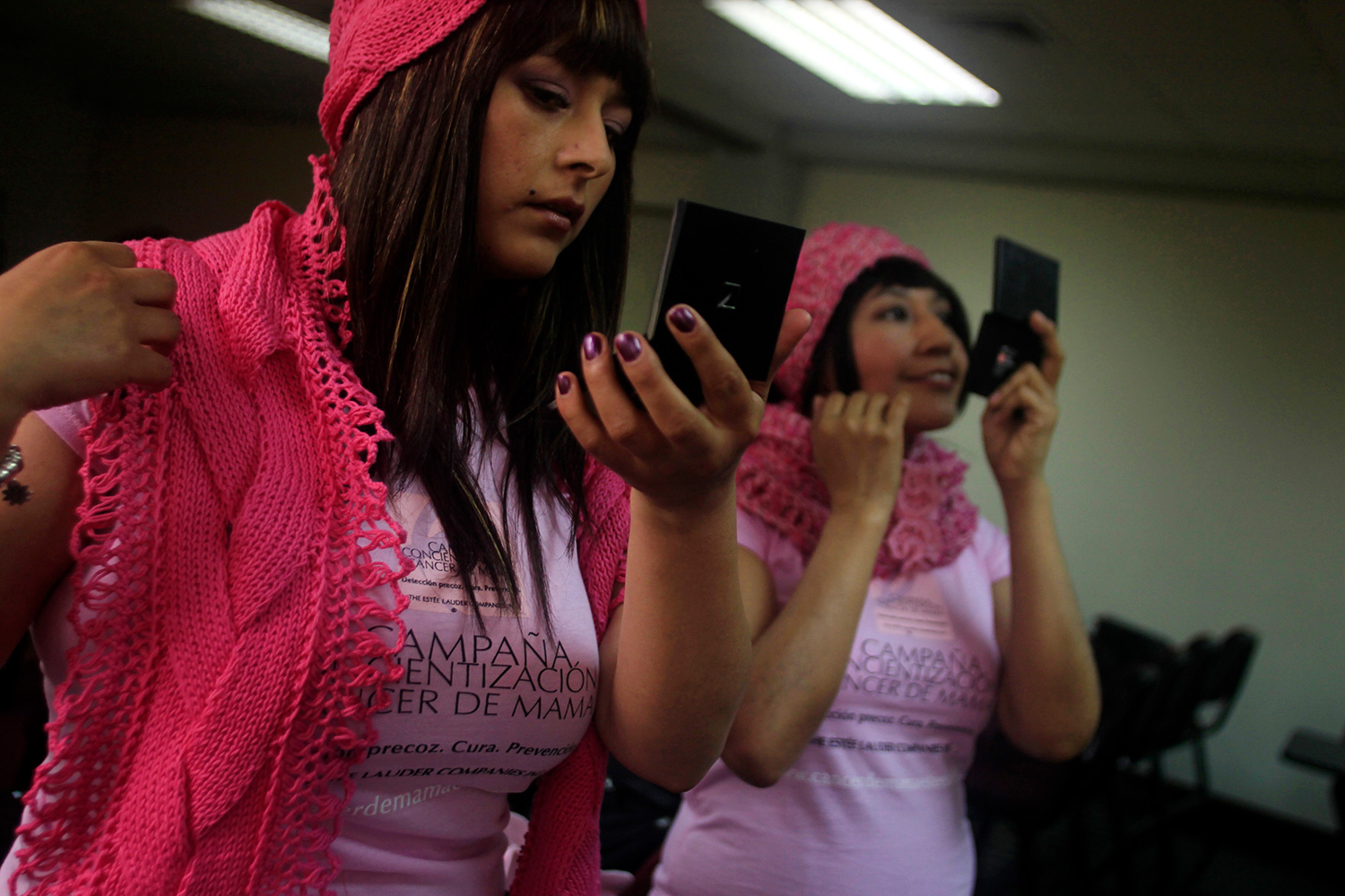 The photo shows two women in pink outfits looking into small mirrors and applying makeup.