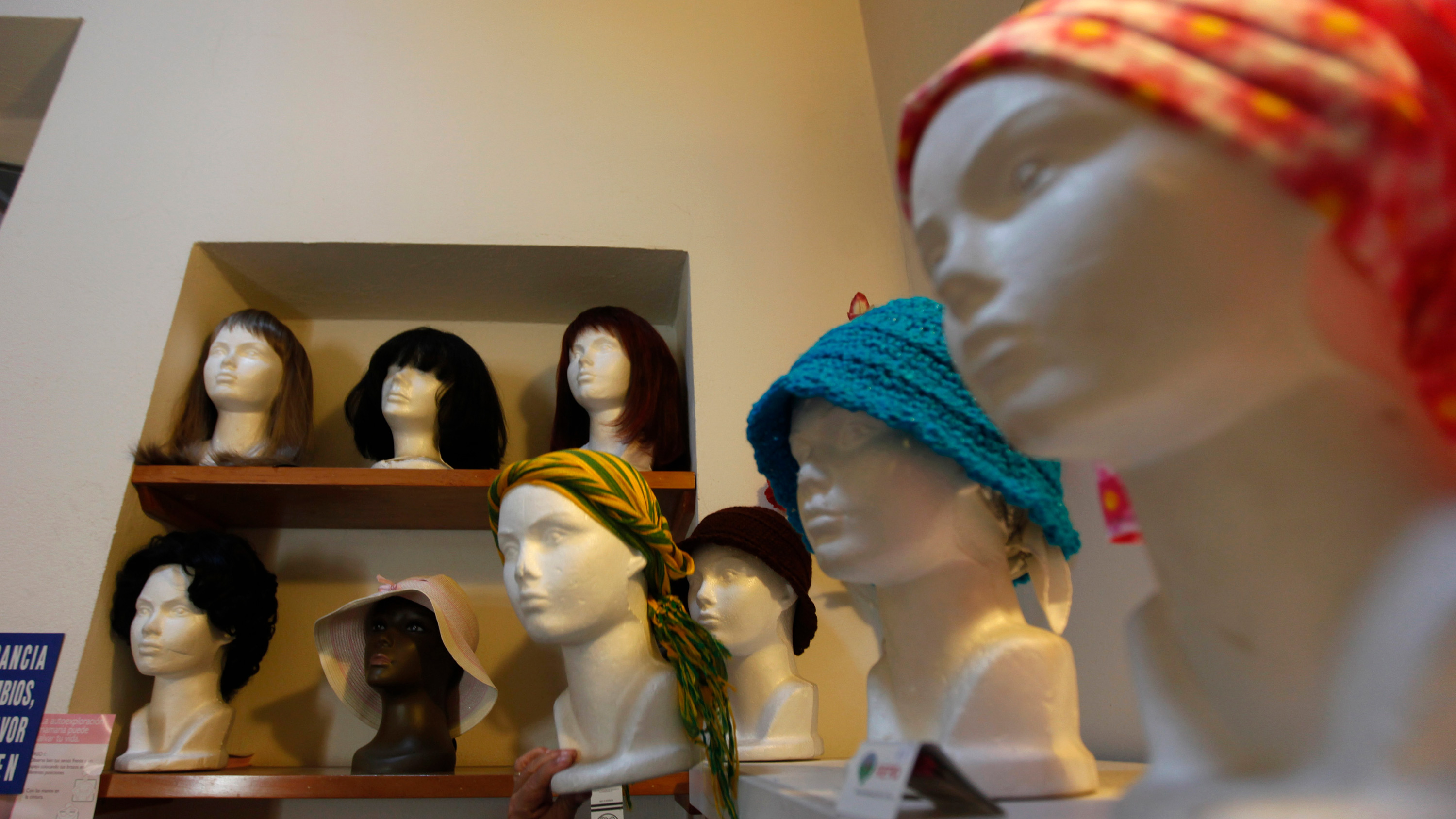 The photo shows a room with mannequin heads and wigs.