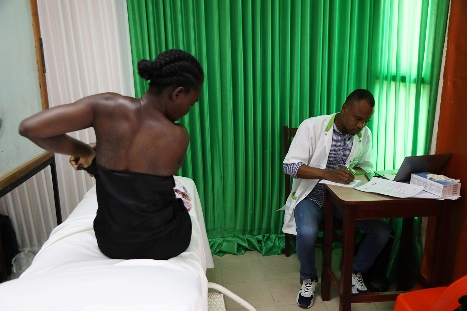 The photo shows the woman on a bed while a doctor sits in a chair next to her. She is in the process of undressing.