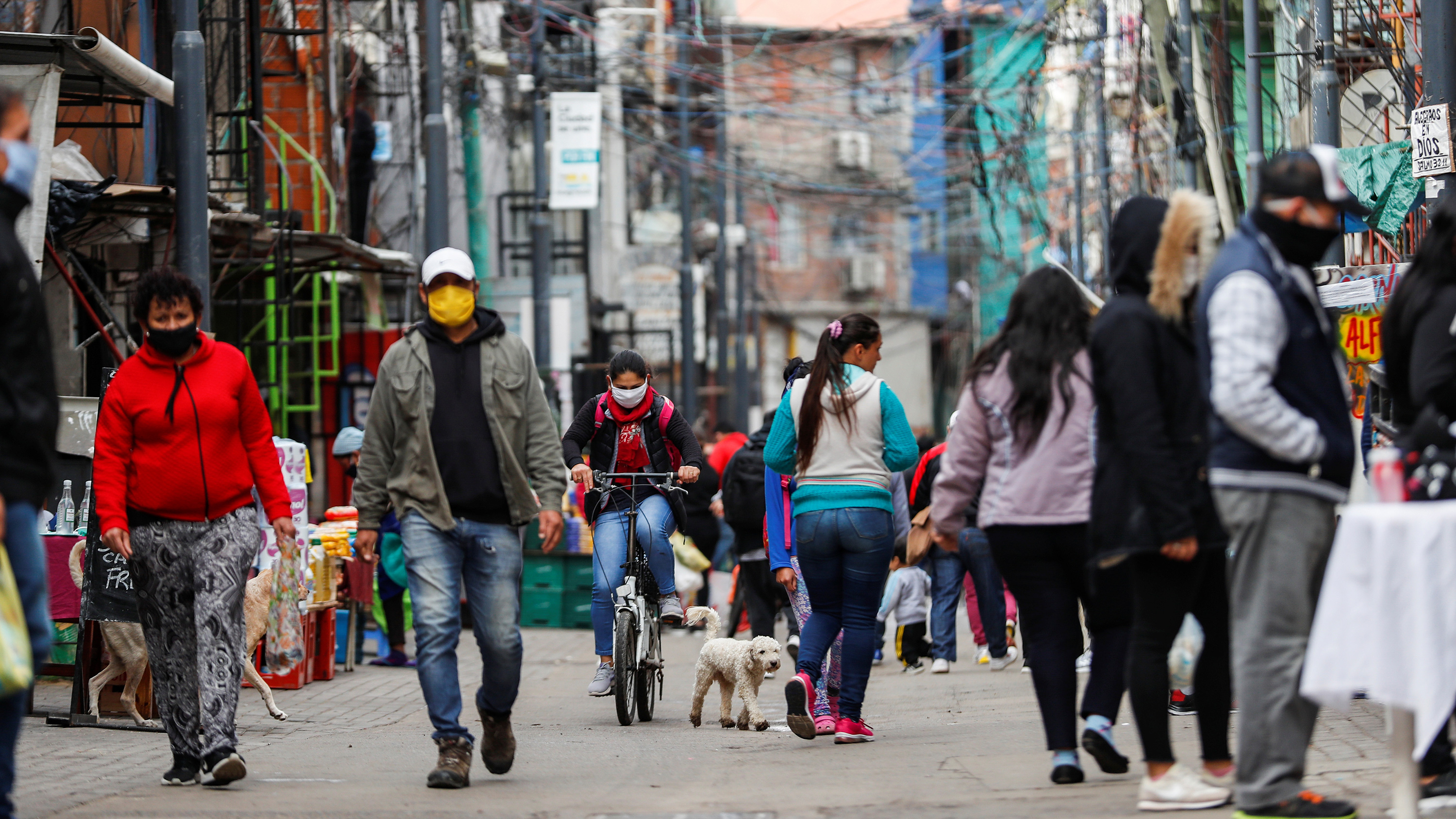 Picture shows a neighborhood street scene with lots of people wandering the streets wearing facemasks.