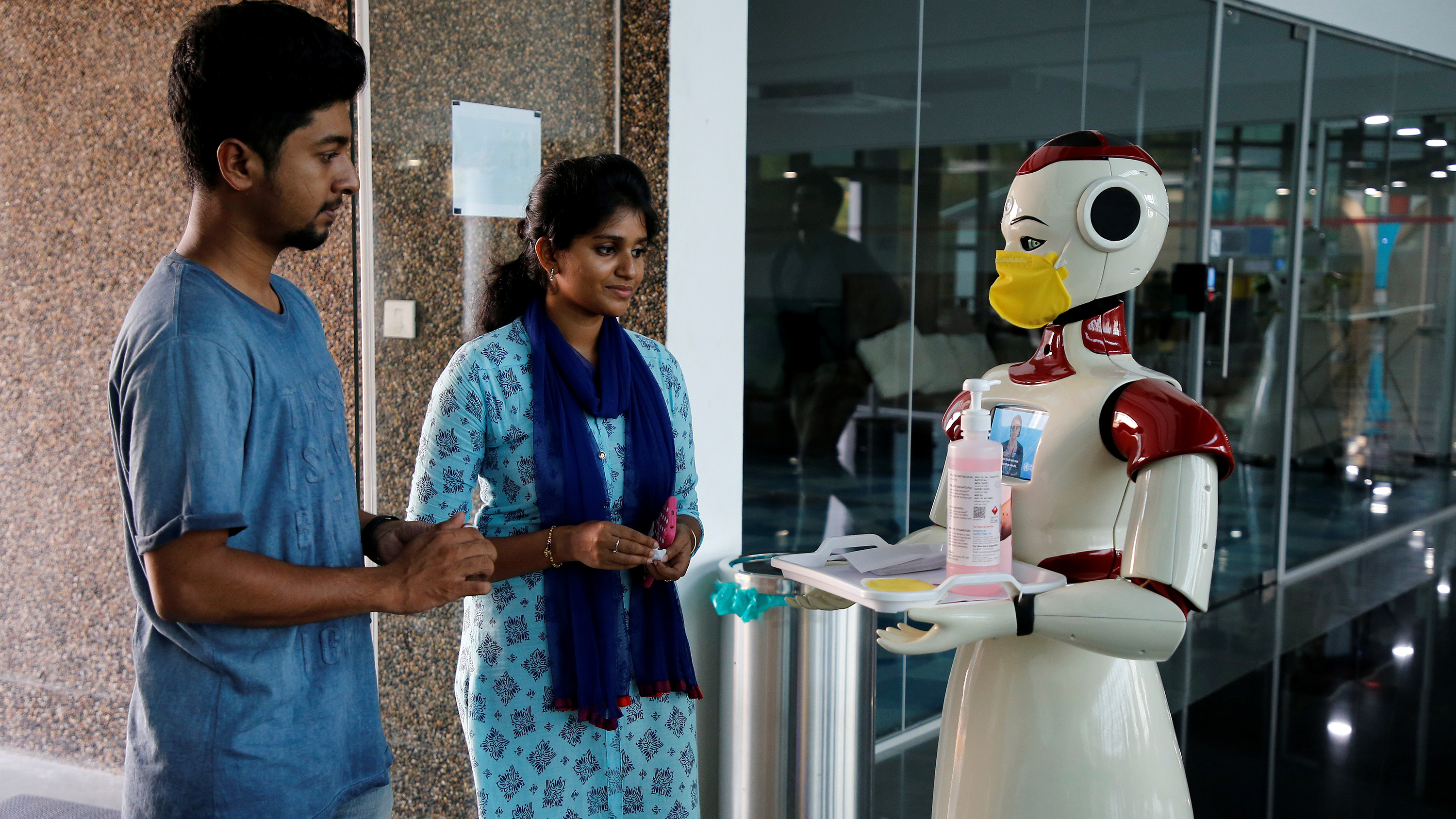 The photo shows two people smiling as they interact with the large, slick robot.