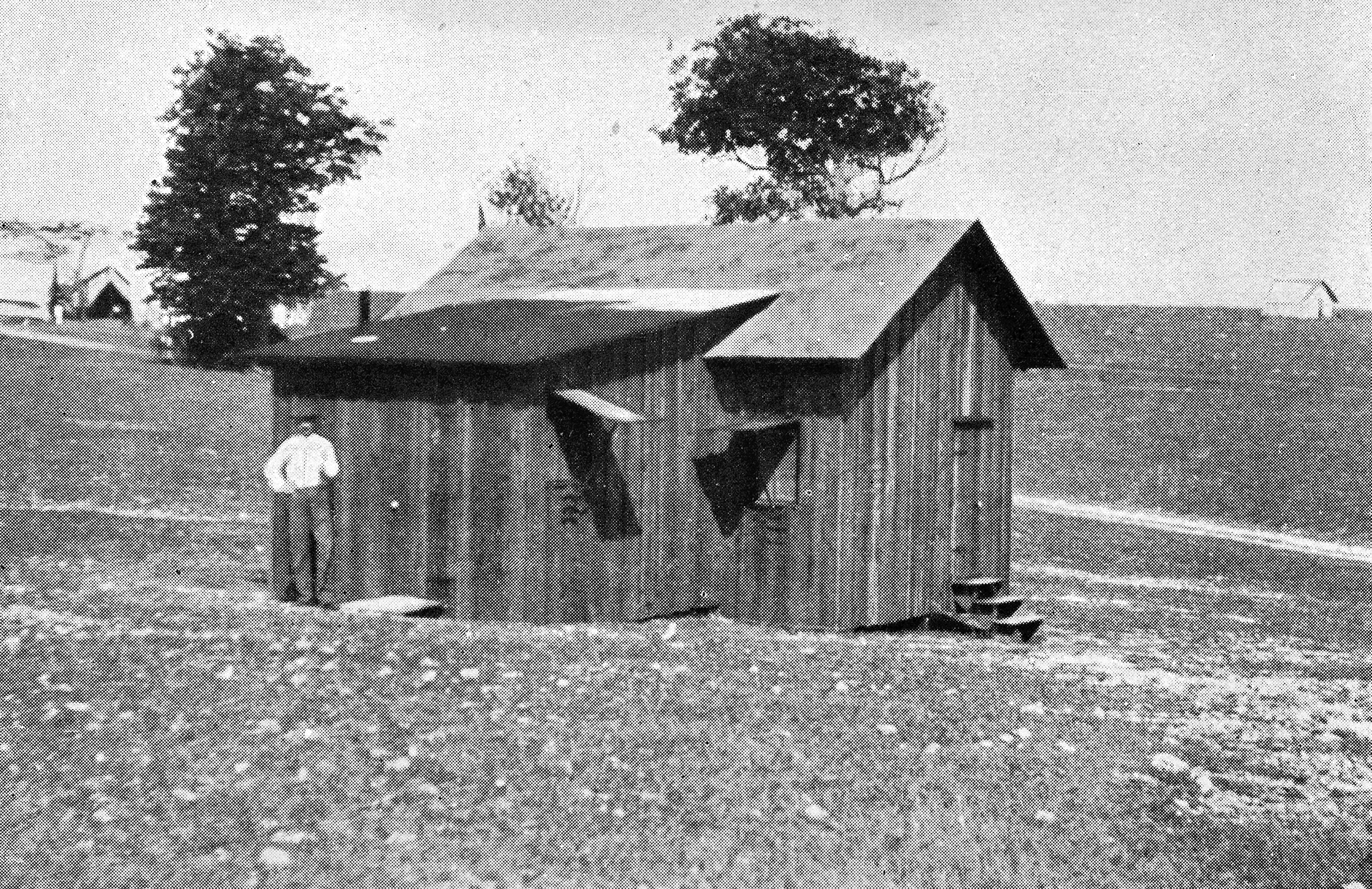 The historic photo shows a wooden hut of a building in a desolate setting with a man standing out front.