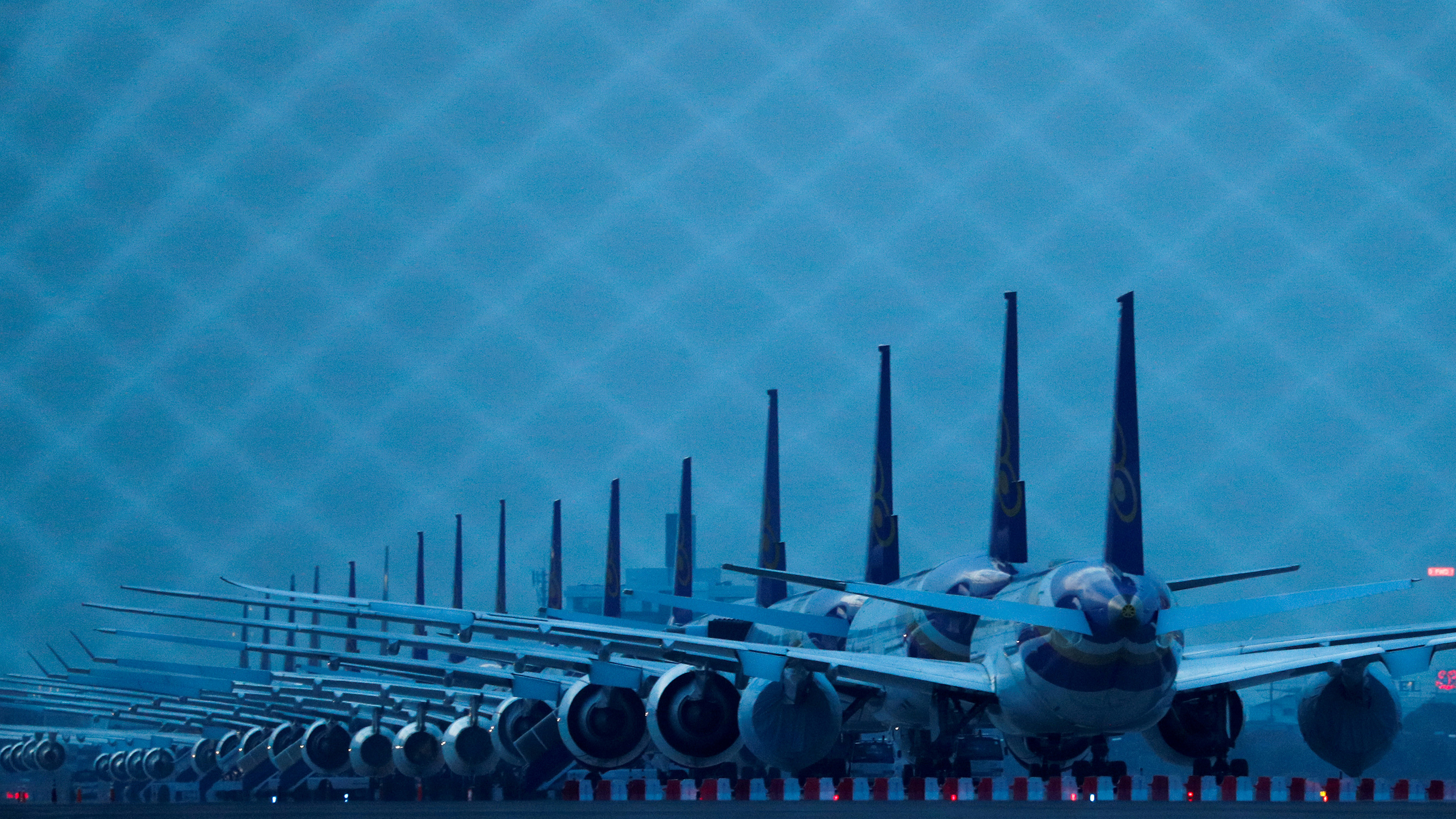 The photo shows a row of airplanes at dusk in a dark blue light.