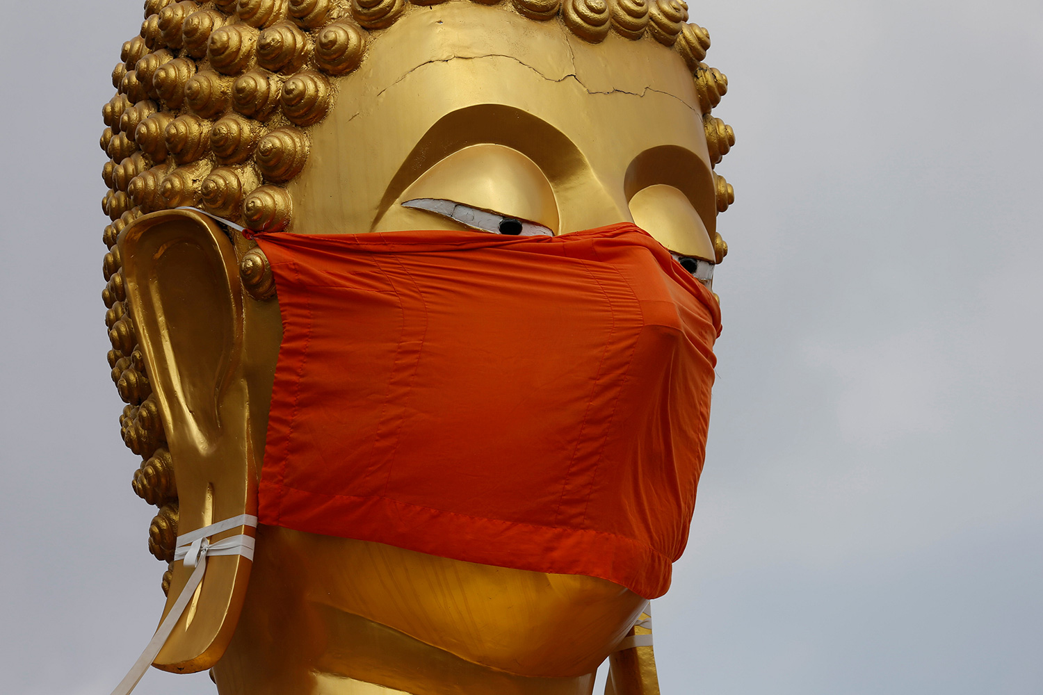 The image shows a golden headed Buddha wearing a bright red mask.